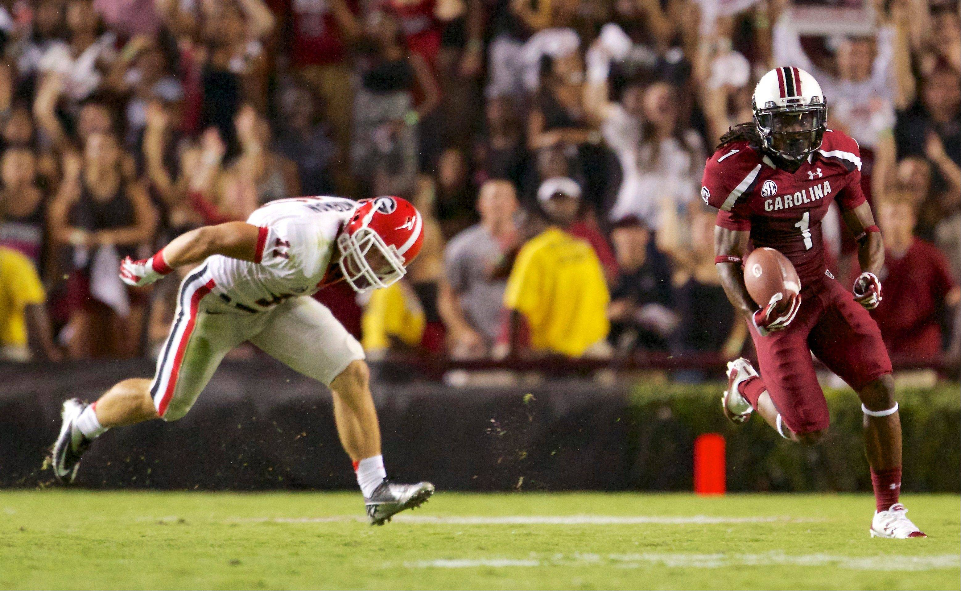 South Carolina�s Ace Sanders, right, breaks away from Georgia�s Connor Norman on a kick return during the second half Saturday at Williams-Brice Stadium in Columbia, S.C.