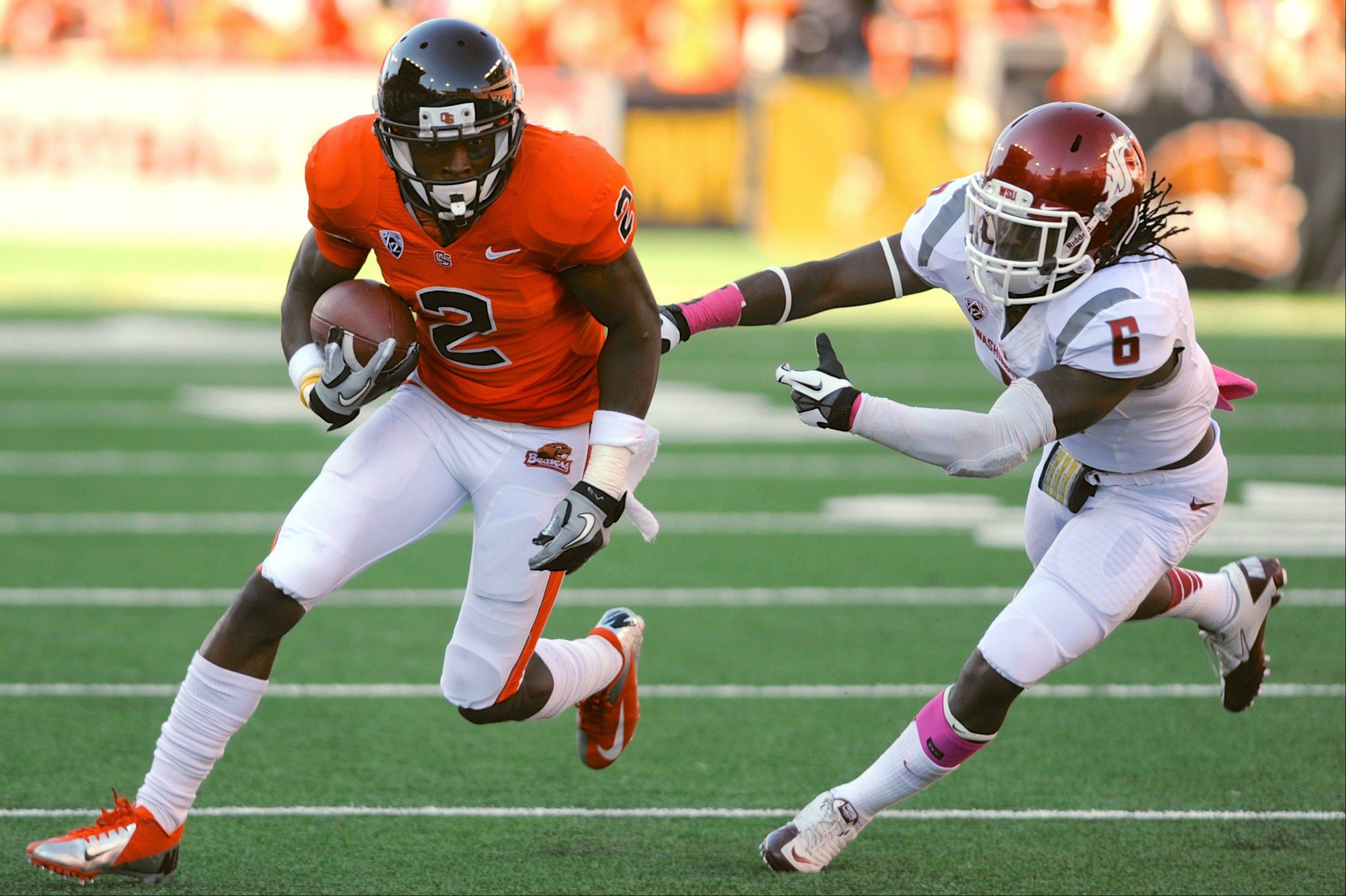 Oregon State�s Markus Wheaton runs against Washington State�s Damante Horton during the first half Saturday in Corvallis, Ore.