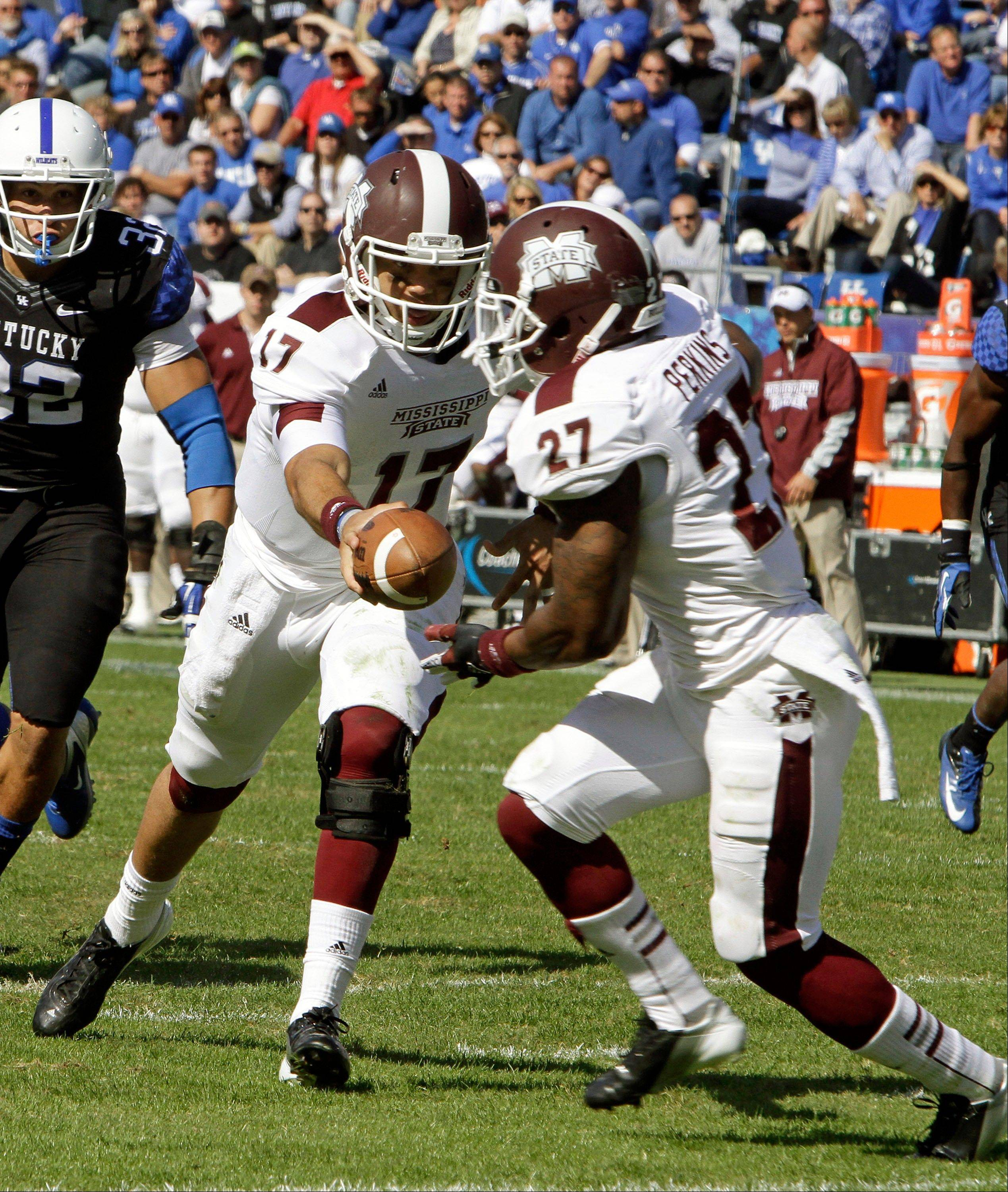 Mississippi State quarterback Tyler Russell hands the ball off to running back LaDarius Perkins on a second-half run against Kentucky on Saturday in Lexington, Ky..