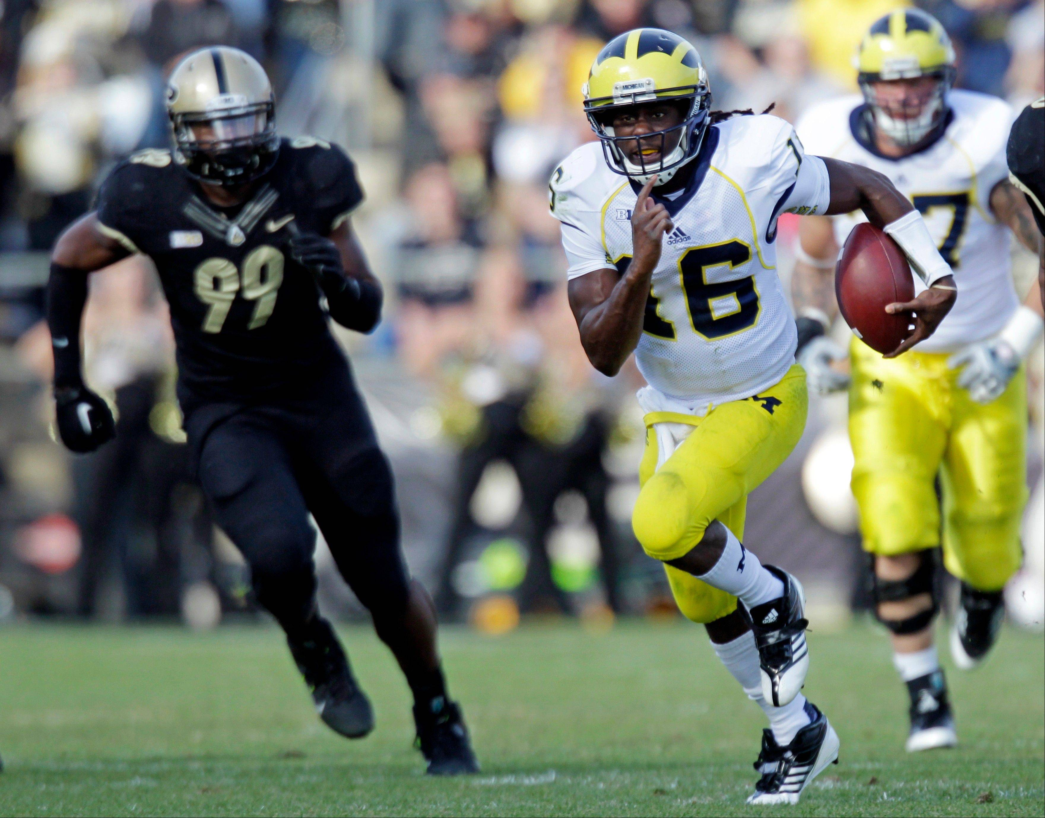 Michigan quarterback Denard Robinson gets past Purdue defensive end Ryan Russell as he picks up 38 yards Saturday during the first half in West Lafayette, Ind.