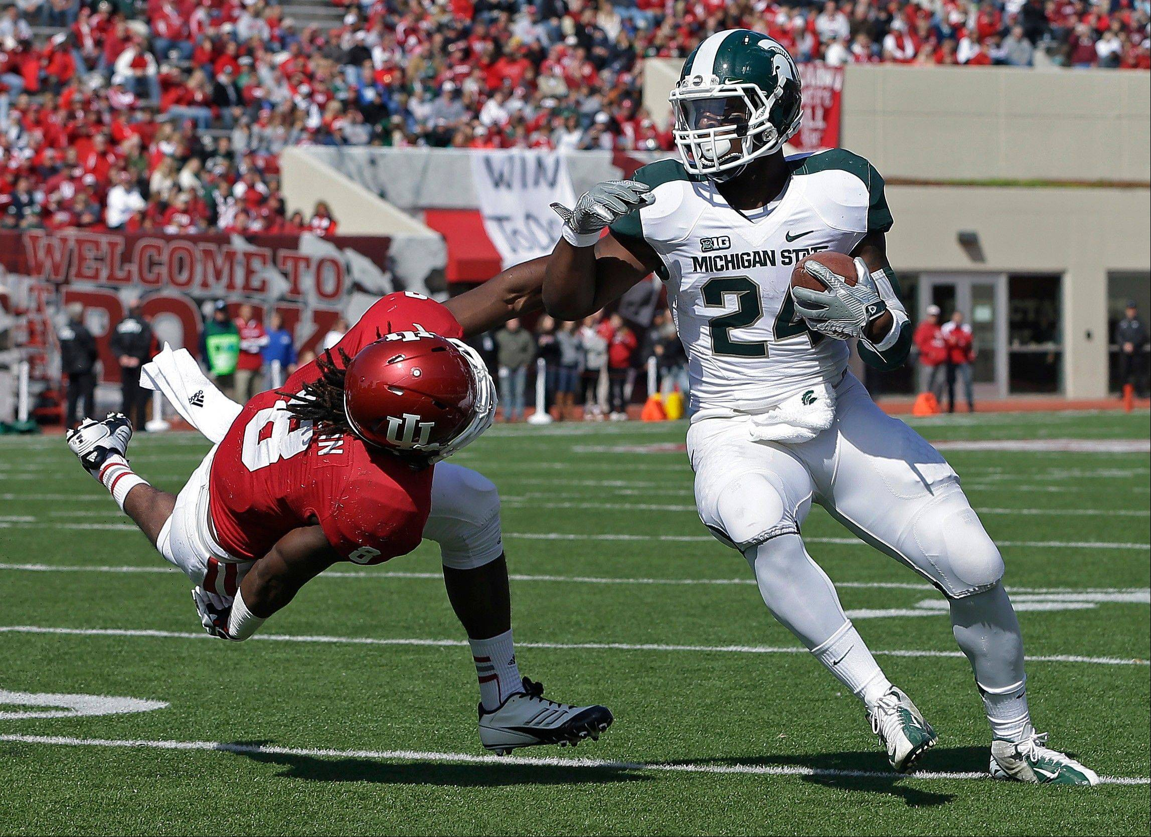 Michigan State running back Le'Veon Bell is tackled by Indiana safety Drew Hardin Saturday during the first half in Bloomington, Ind.