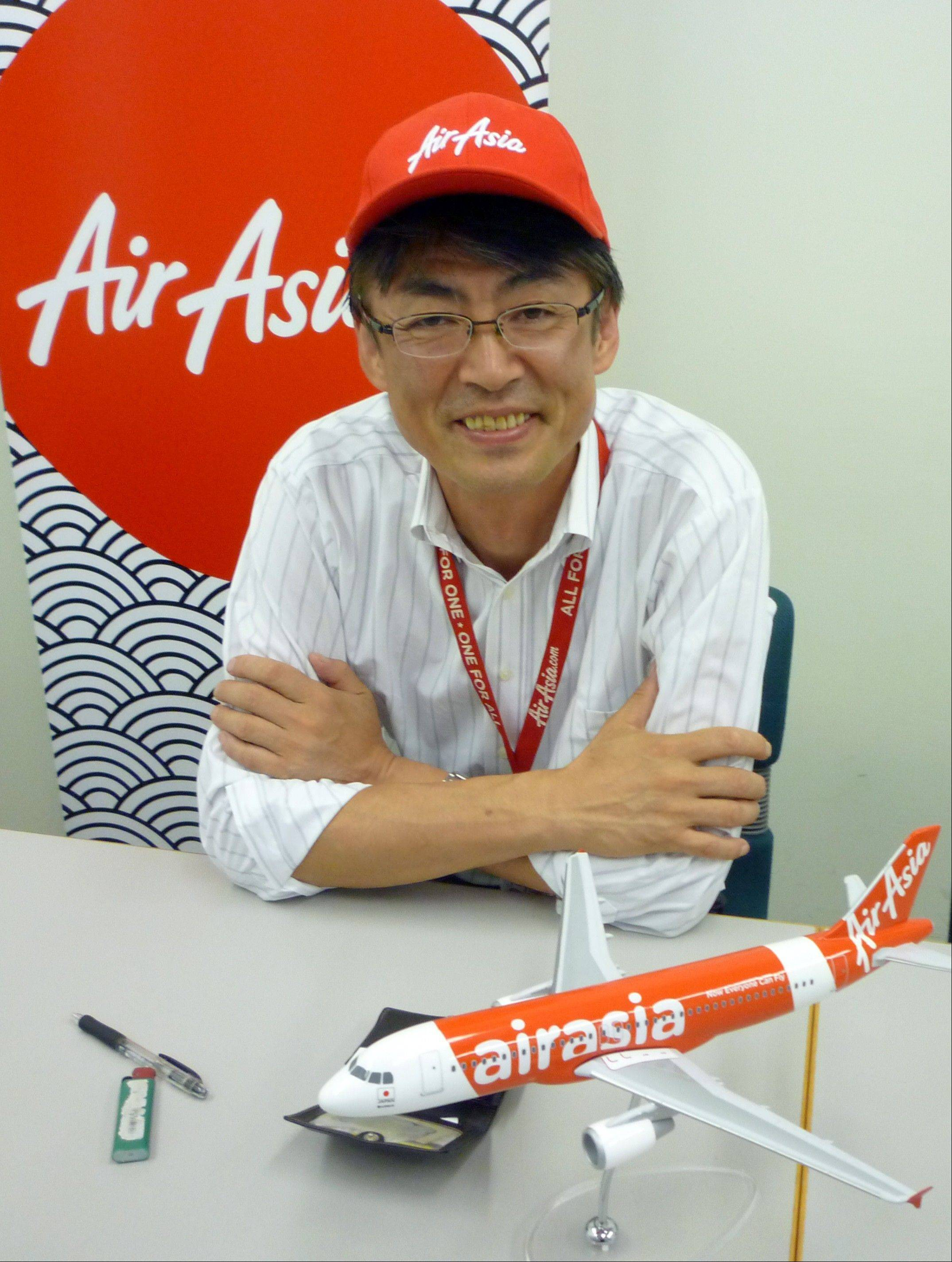 "AirAsia Japan President Kazuyuki Iwakata smiles during an interview in Tokyo. ""It's not that the meals on standard fares were ever free. The charge was just part of the ticket price,"" Iwakata told The Associated Press. ""With us, people pay only for what they need."" As a marketing ploy, AirAsia Japan, which started operations in August, offered tickets for just 5 yen (5 cents) to the first 10,000 people. They quickly sold out."