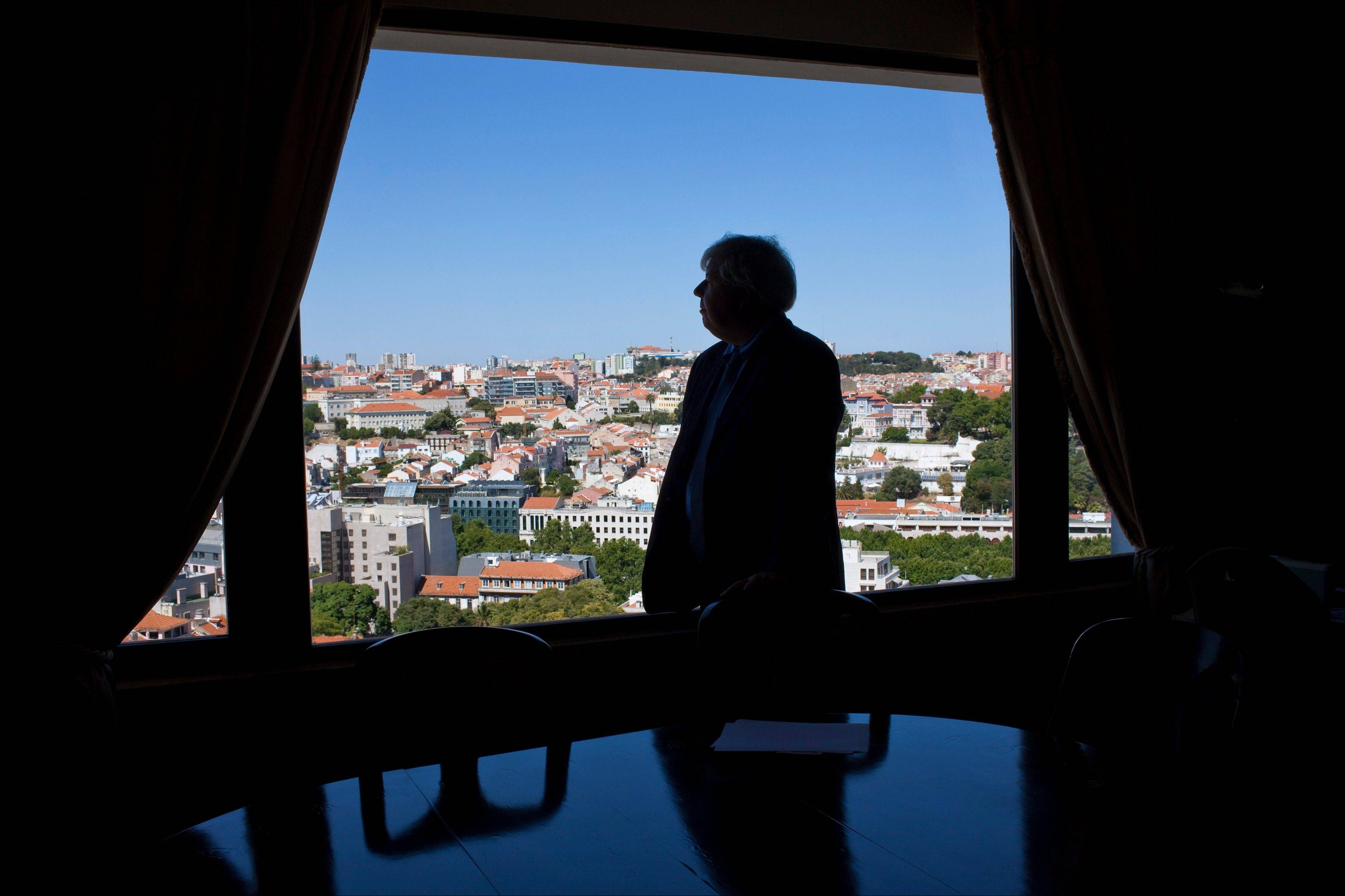 Luis Menezes Leitao, president of the Lisbon Property Owners' Association, looks out of the window of his office at the association's headquarters in Lisbon's upper-class Principe Real neighborhood during an interview.