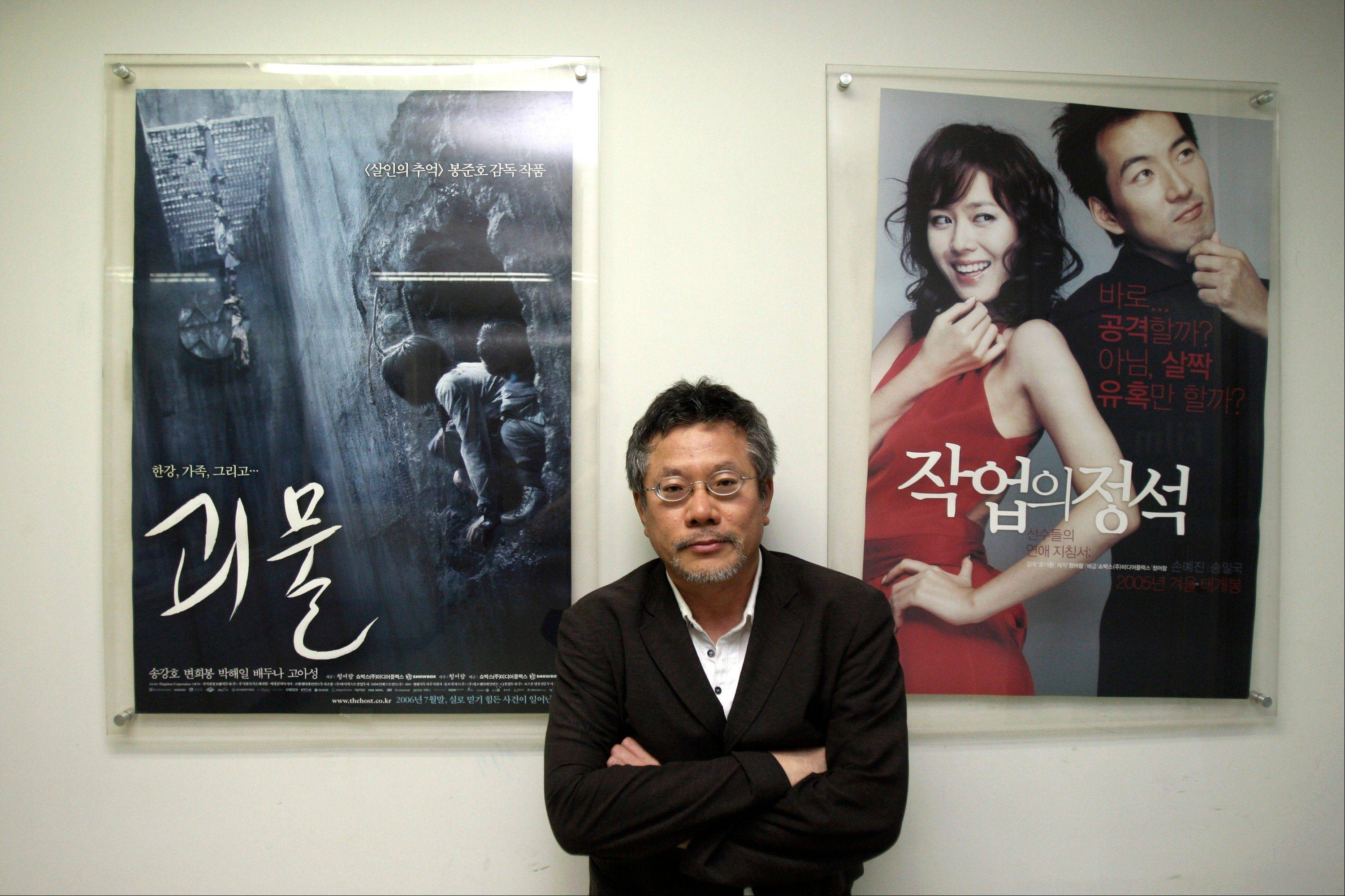 Choi Yong-bae, Chungeoraham Film CEO and Producer, poses with posters produced by his company during an interview with The Associated Press at his office in Seoul, South Korea. After being turned down by many investors over the last four years, Choi said it feels strange and exciting that his revenge film about a notorious South Korean president blamed for the massacre of democracy protesters is finally coming to life through online donations.
