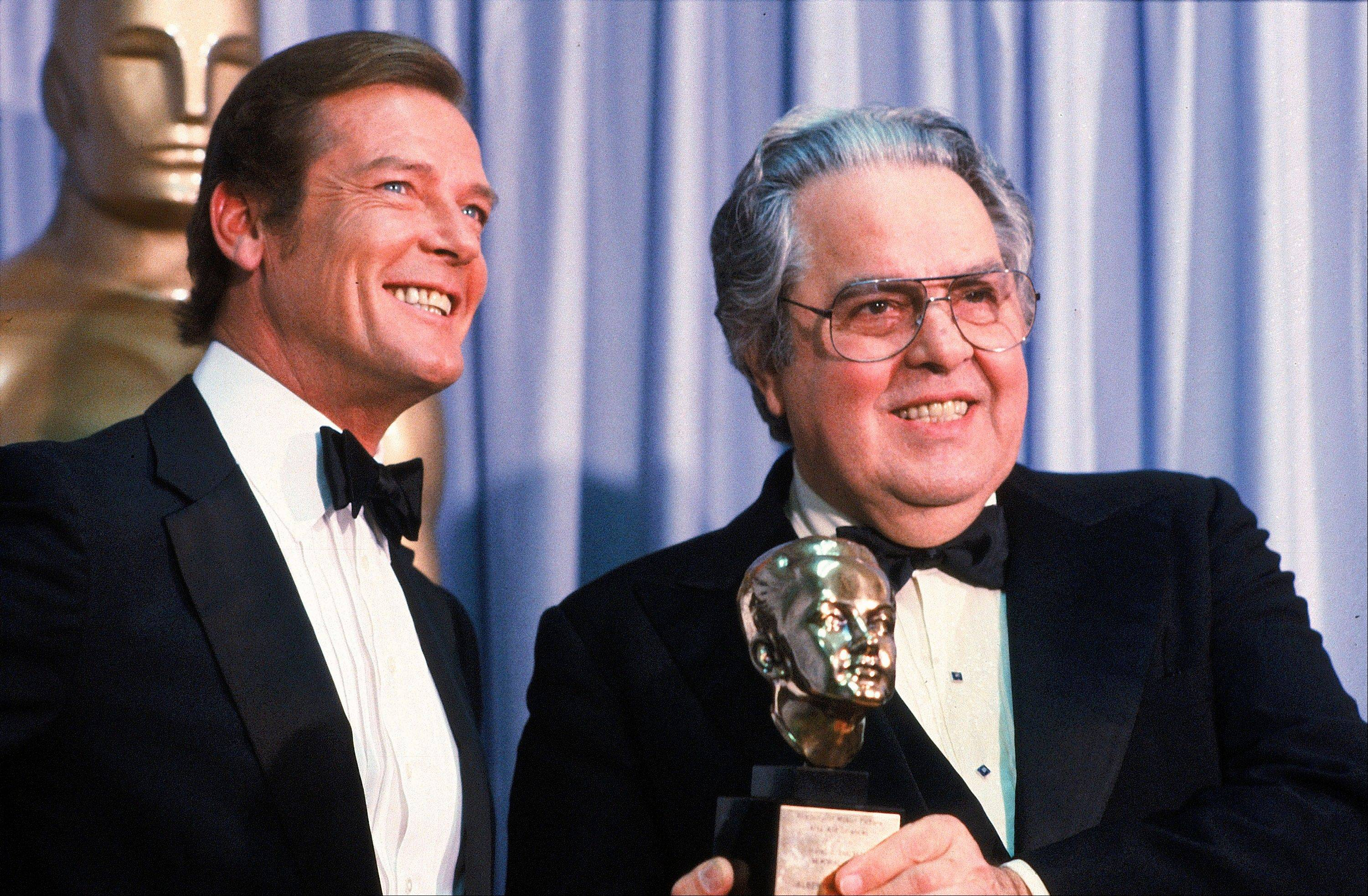 "In this March 29, 1982 file photo, Albert ""Cubby"" Broccoli, producer of the ""James Bond"" series, holds the Thalberg Award he received for his work at the Academy Awards, in Los Angeles. Roger Moore, left, British actor who plays secret agent 007 James Bond, made the presentation."