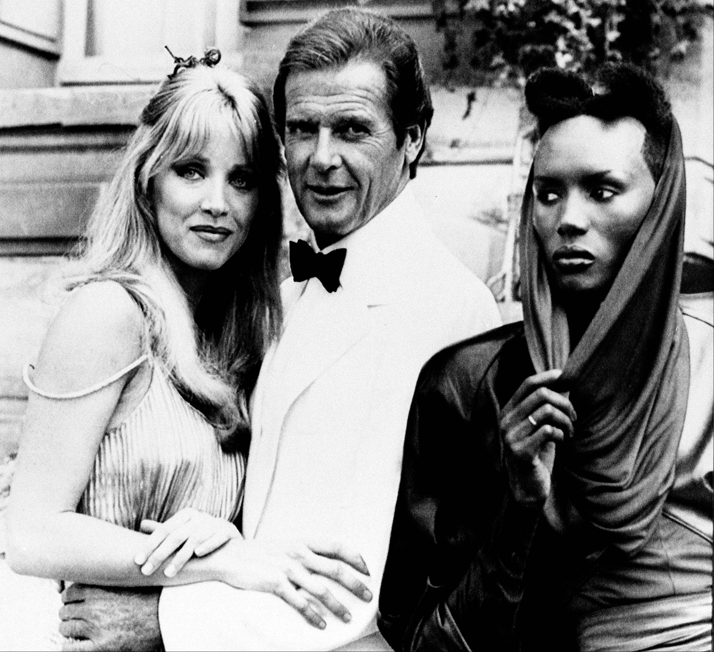 "In this Aug. 17, 1984 file photo, actor Roger Moore, alias British secret agent James Bond, is seen with his co-stars Tanya Roberts, and Grace Jones, right, in front of Chateau de Chantilly, on the set of the 007 action film ""A View to a Kill,"" near Paris, France."