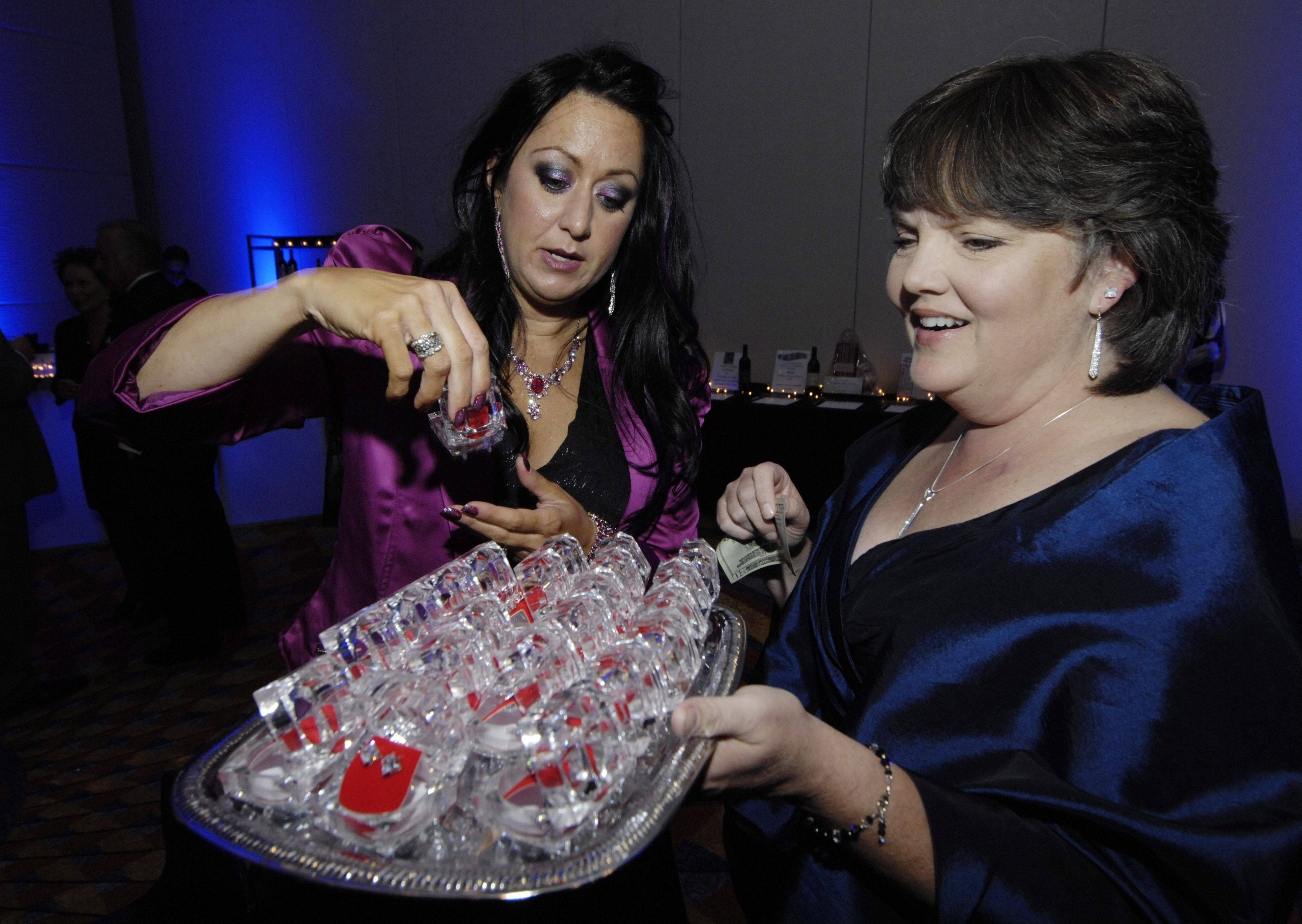 Kari-Ann Ryan of Schaumburg makes a selection for the diamond earring raffle with the assistance of volunteer Kathy Atwell of Schaumburg during the Schaumburg Business Association gala and awards Saturday at the Renaissance Convention Center Hotel.