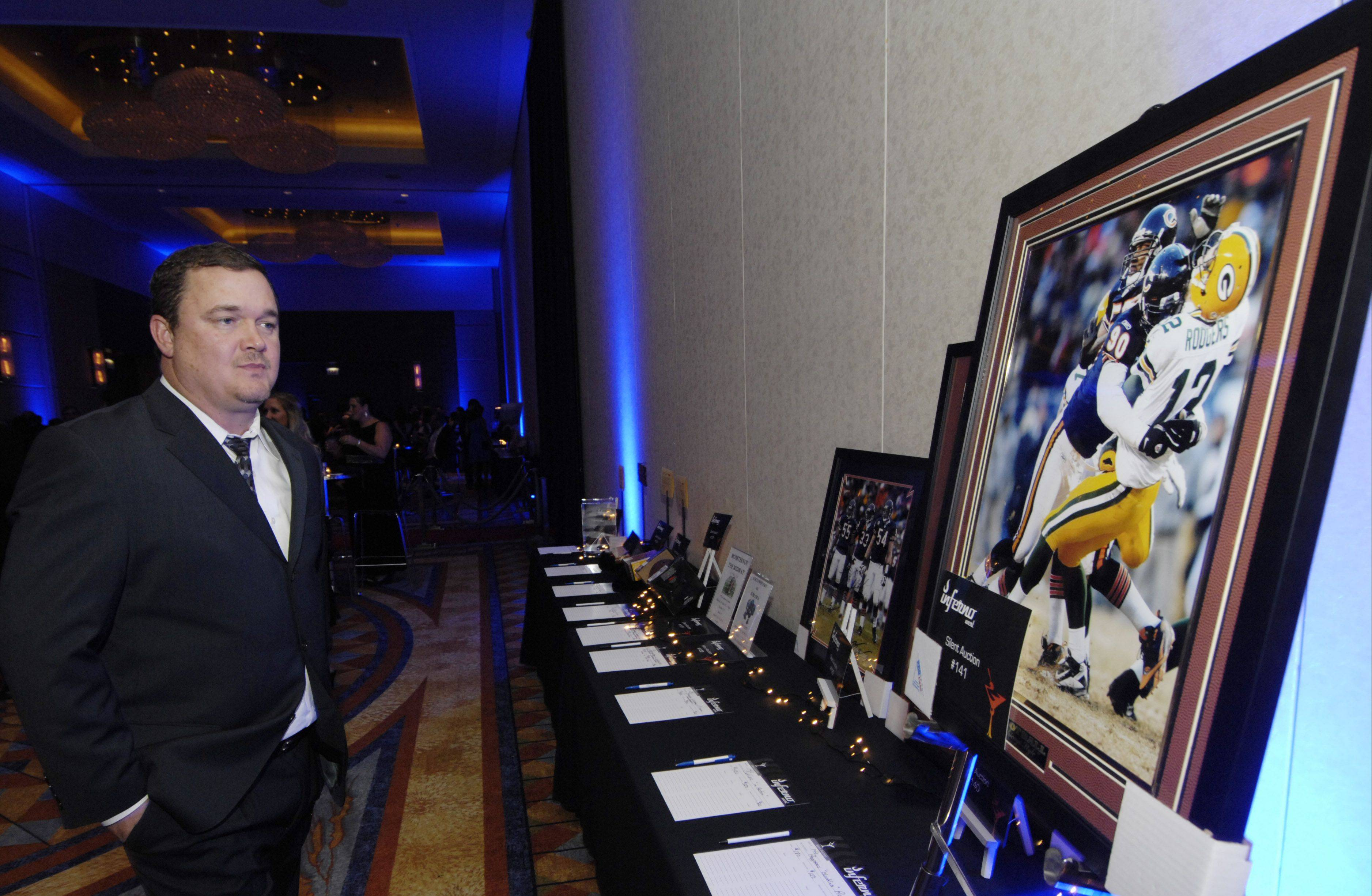 Cory Baldwin of Arlington Heights views silent auction items including Bears action photos during the Schaumburg Business Association gala and awards Saturday at the Renaissance Convention Center Hotel.