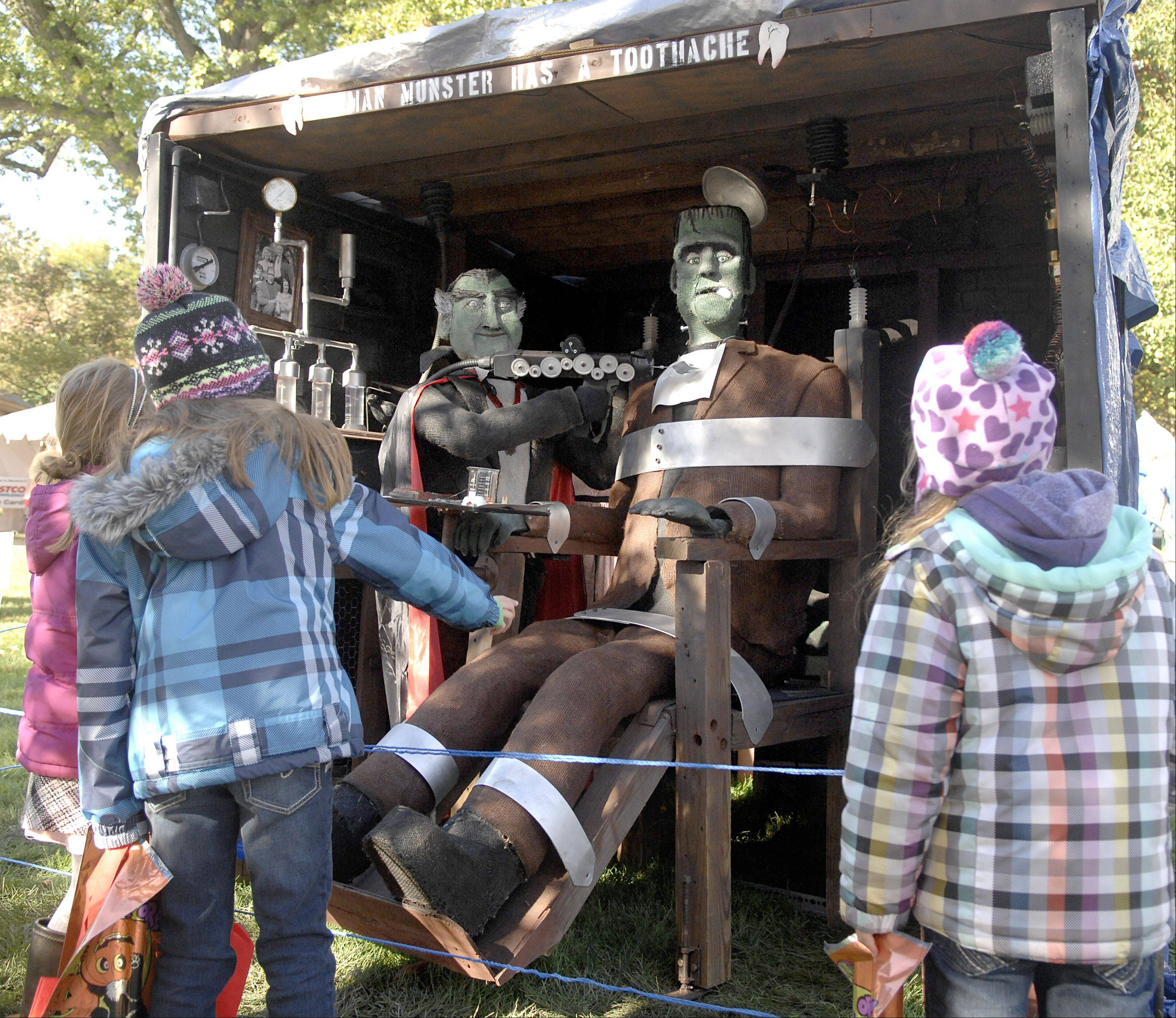 "Maren Wallace, 6, of St. Charles, left, joins friends Madison Kunzer, 8, and her sister, Emily, 6, of Elburn to watch the movements of ""Herman Munster Has a Toothache,"" an entry in the mechanical category, at the St. Charles Scarecrow Fest on Saturday."