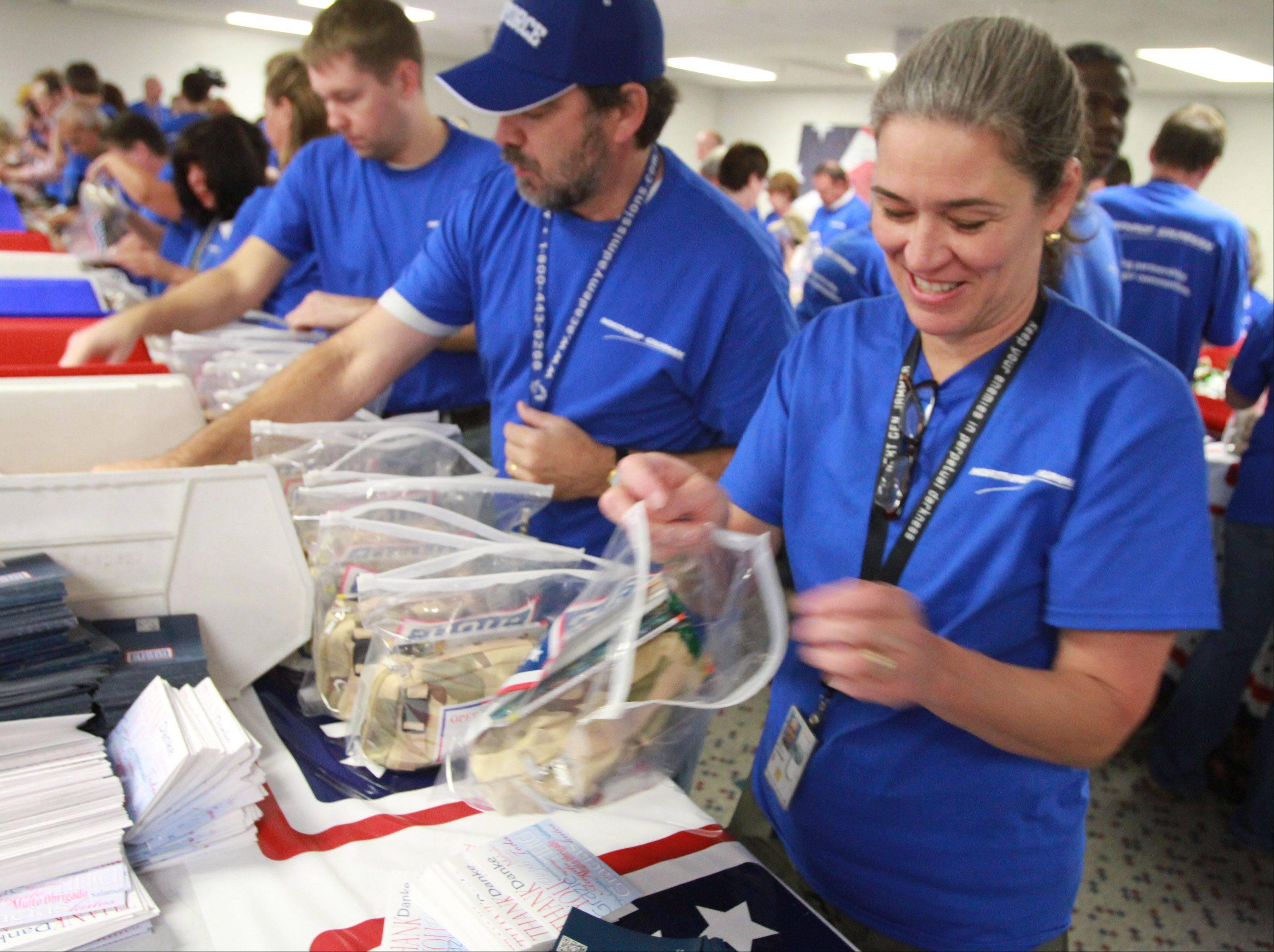 Janine Nyre of Lake Barrington, a vice president at Northrop Grumman's Rolling Meadows operation, stuffs USO care packages Saturday.