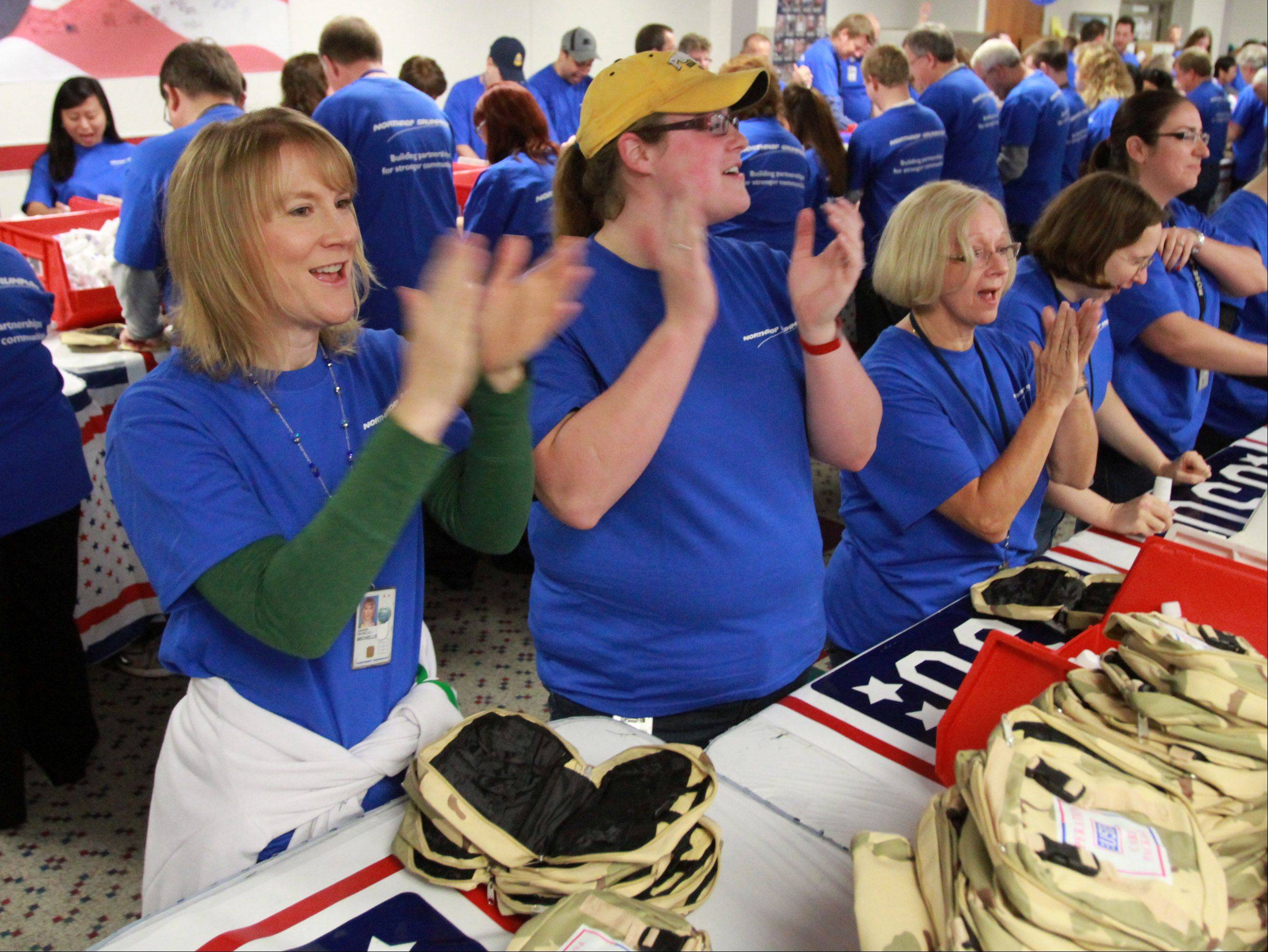 Northrop Grumman employees including Michelle Anders of Bartlett, far left, and Kari Parson of Plainfield, right, celebrate filling a large container with USO care packages.