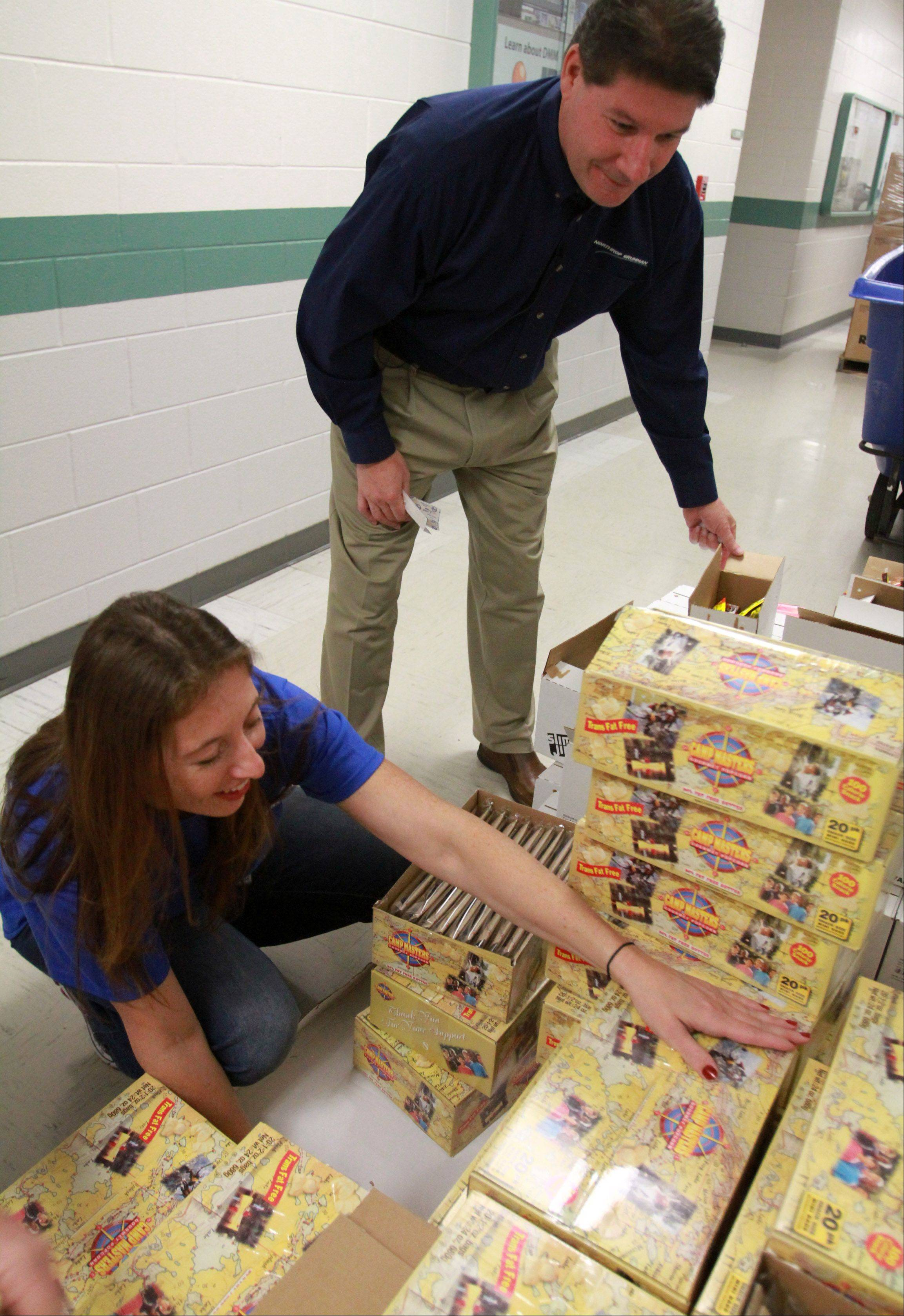 Jeffrey Palombo, sector vice president of Northrop Grumman, and employee Nadine DiSpirito of Arlington Heights unpack items to be stuffed into USO care packages at the company offices in Rolling Meadows on Saturday.