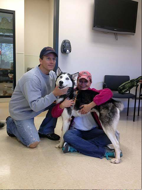 Heather Jackson of Chatsworth, Ga., and her brother, Matthew Asbury, embrace Shakira, a 6-year-old female Siberian husky who had been missing for nearly five years.
