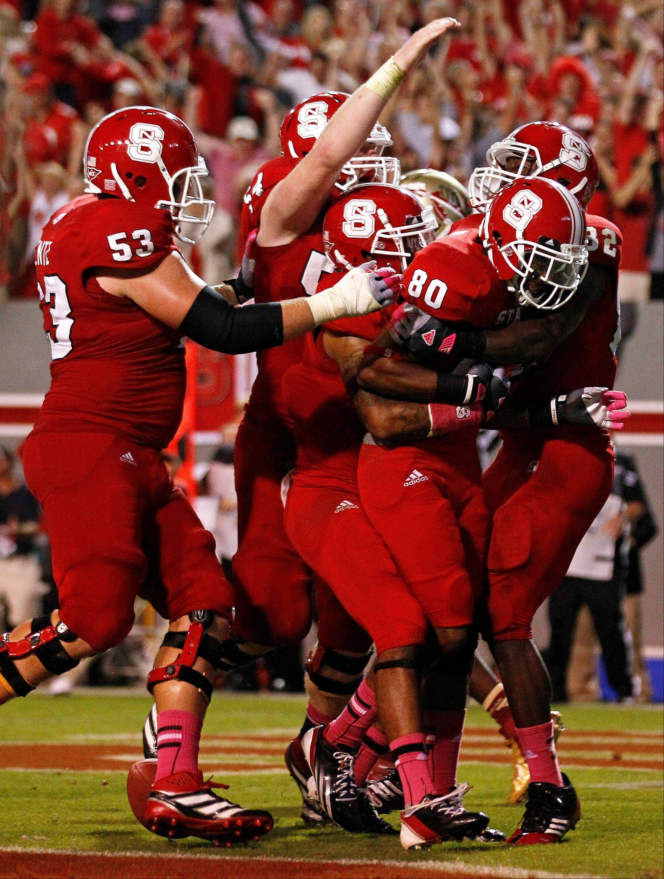 North Carolina State's Bryan Underwood (80) is congratulated by teammates after his touchdown to tie the game late in the second half Saturday against Florida State in Raleigh, N.C.