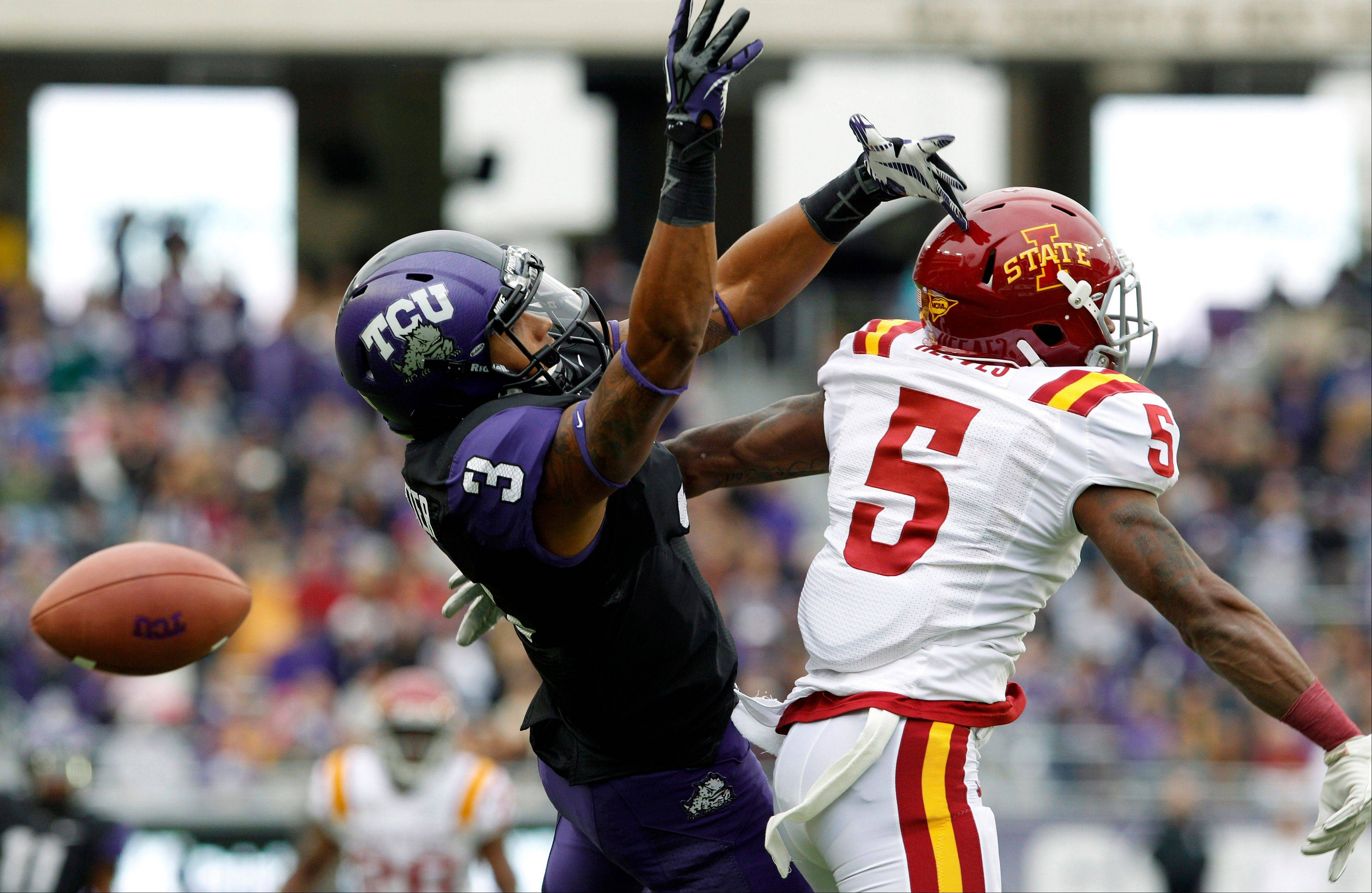 TCU wide receiver Brandon Carter and Iowa State defensive back Jeremy Reeves jump for a pass that fell incomplete during the first half Saturday in Fort Worth, Texas.