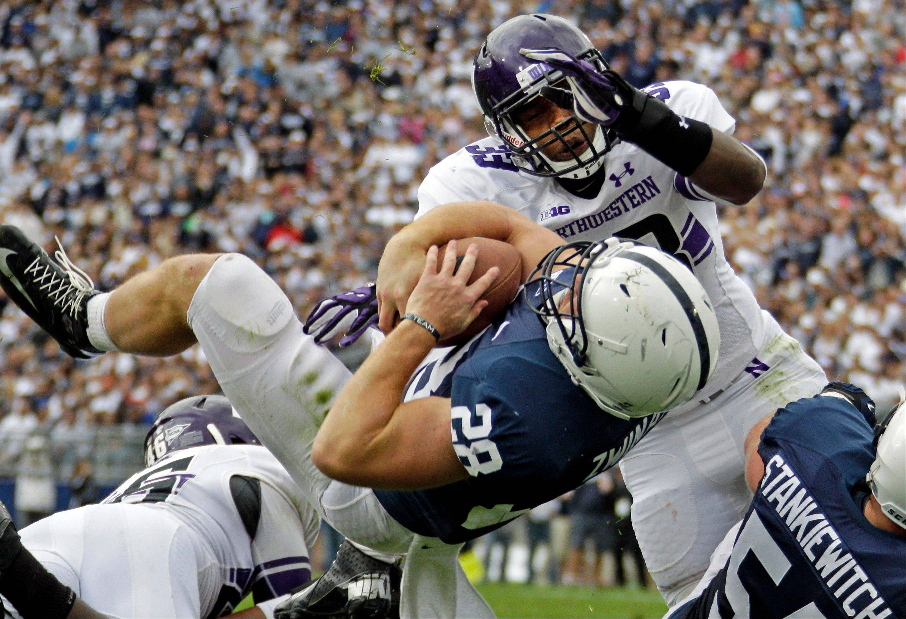 Penn State running back Zach Zwinak dives into the end zone past Northwestern linebacker David Nwabuisi (33) for a touchdown during the second quarter.