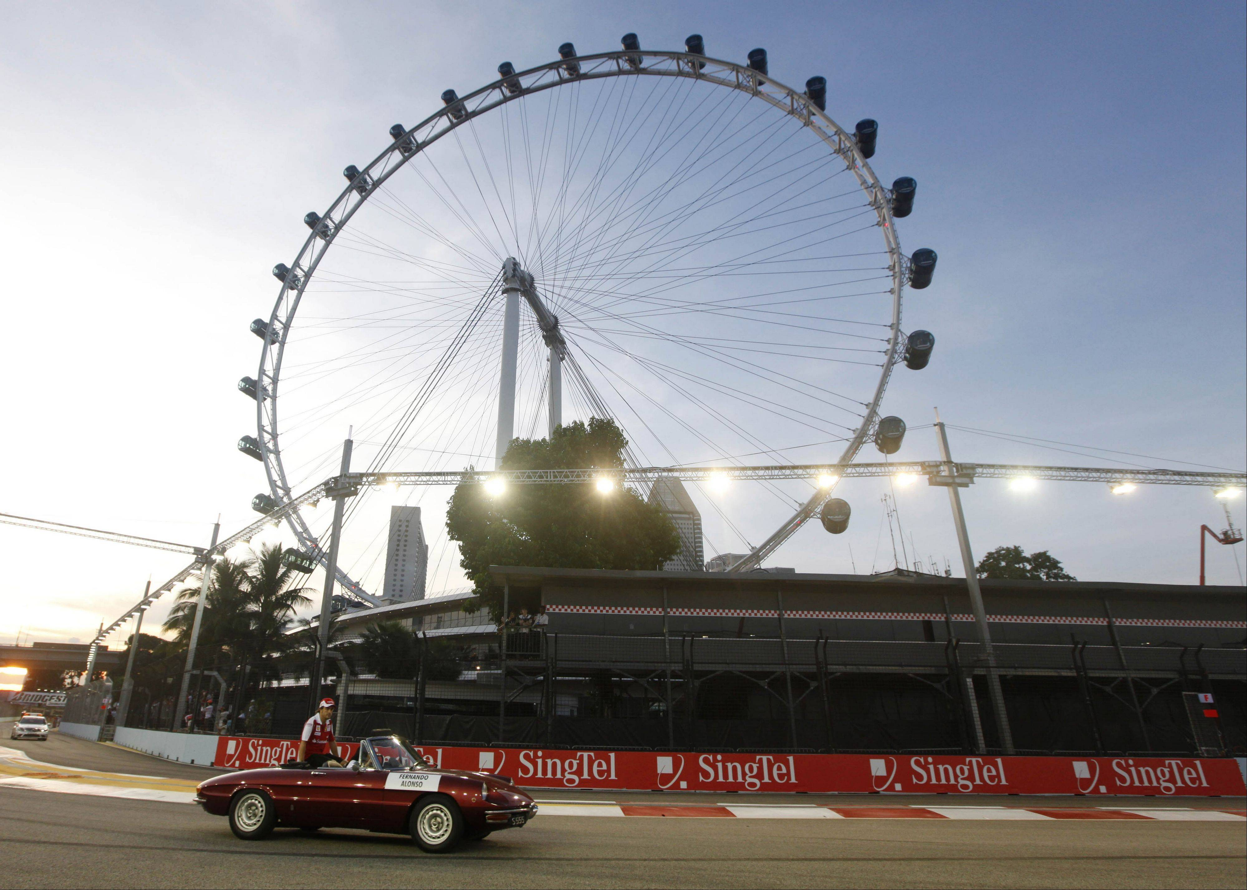 FILE � In this Sept. 26, 2010 file photo, Ferrari Formula One driver Fernando Alonso of Spain is driven past the 541 foot tall �Singapore Flyer� Ferris wheel during the driver� parade prior to the start of the Singapore Grand Prix on the Marina Bay City Circuit in Singapore. The proposed New York Wheel in the Staten Island borough of New York is planned to be 625 feet tall, and expected to open by the end of 2015. (AP Photo/Mark Baker, File)