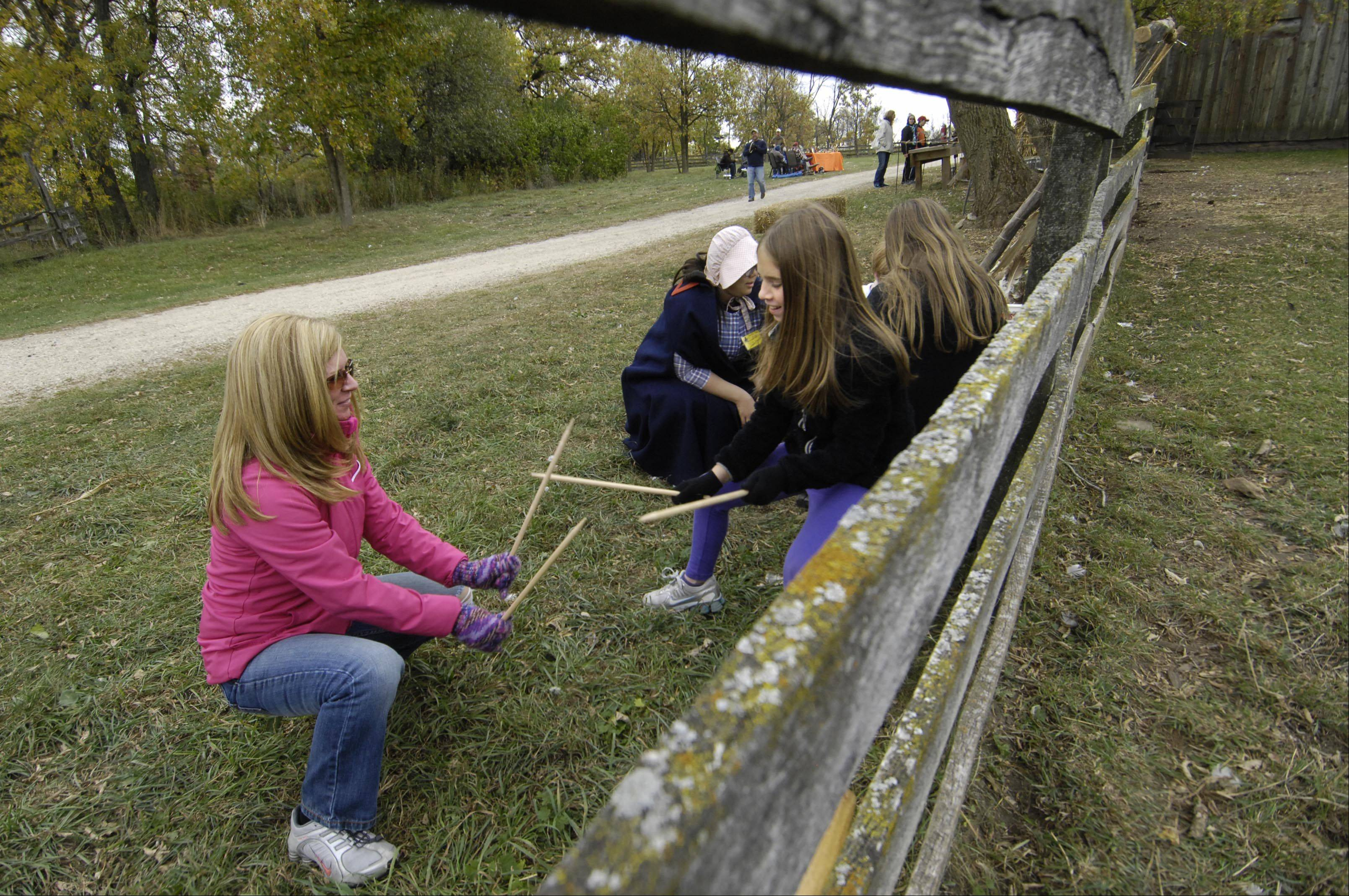 Kim McLaughlin plays an old fashioned game with her daughter Riley, 10, at Sunday's Fall Festival and 35th anniversary of the Garfield Farm Living History Museum and working farm west of Geneva.