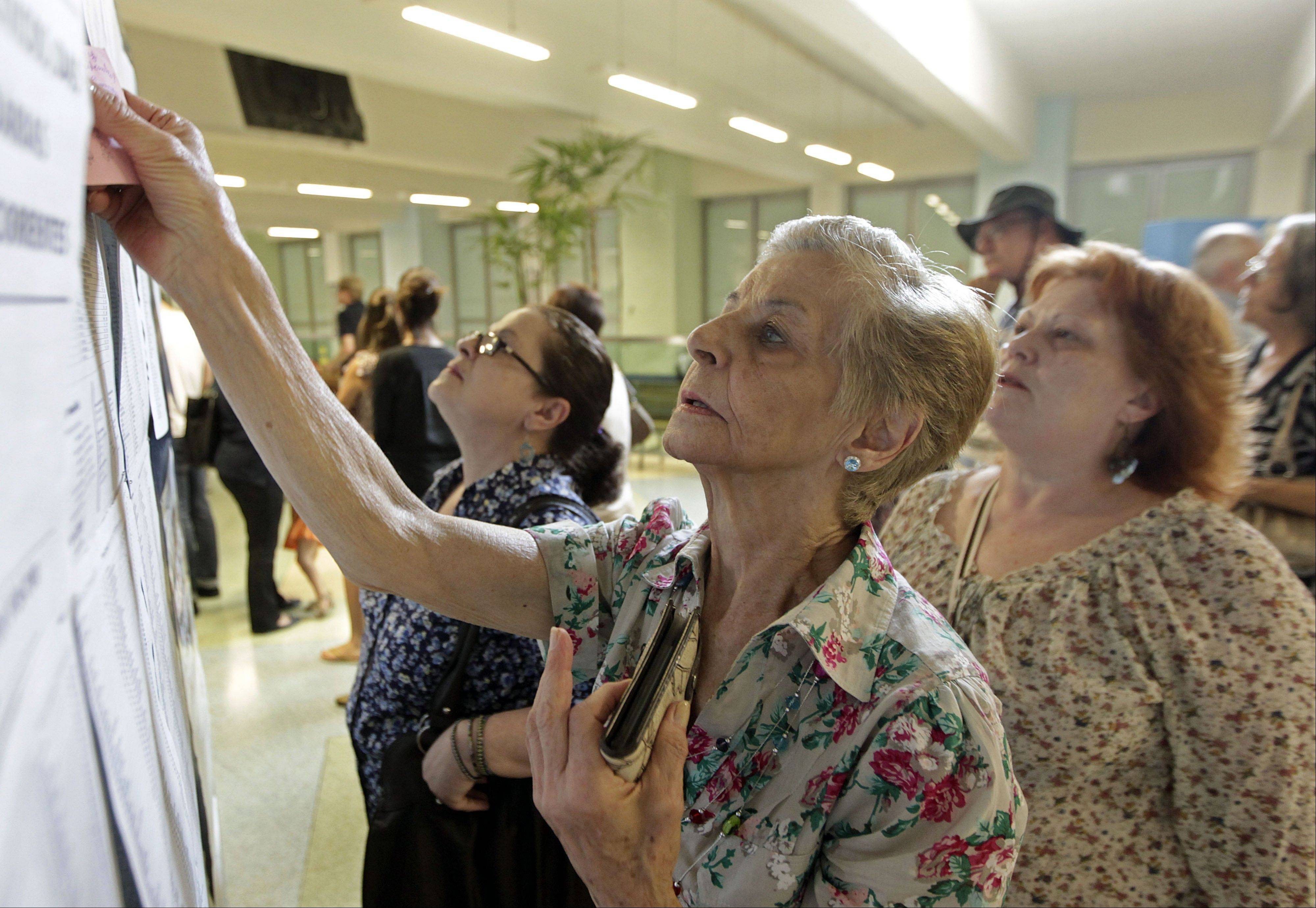 Women check the list of candidates before voting in municipal elections in Sao Paulo, Brazil, Sunday, Oct. 7, 2012. Voters across Latin America�s biggest country are electing mayors and municipal council members.