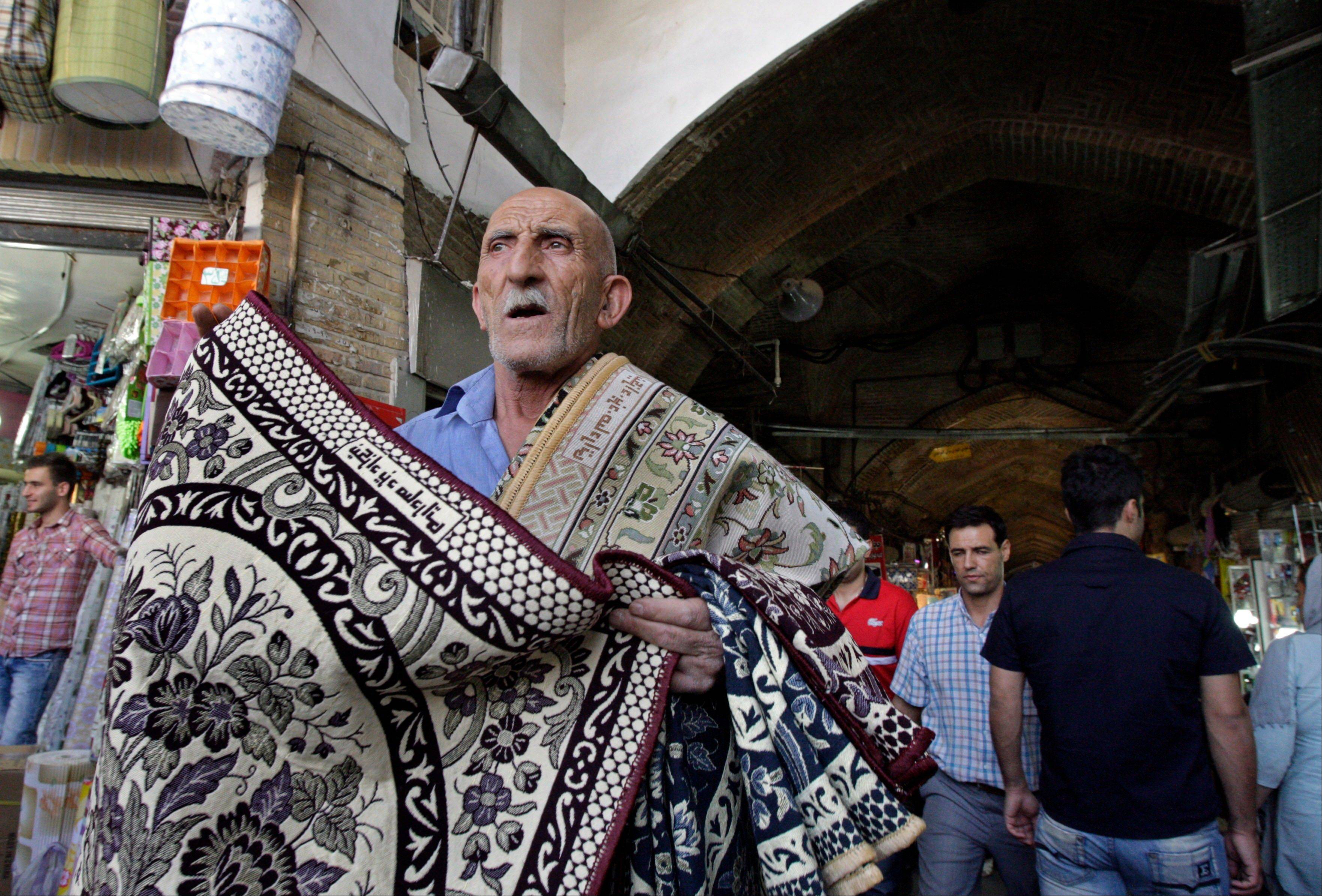 An Iranian man tries to sell carpets Sunday at the main entrance of the Tehran�s old main bazaar in downtown Tehran. Iran�s parliament on Sunday abandoned its planned impeachment of a cabinet minister over the free-fall of the country�s currency, opting instead to look for more effective economic measures, like cutting spending.