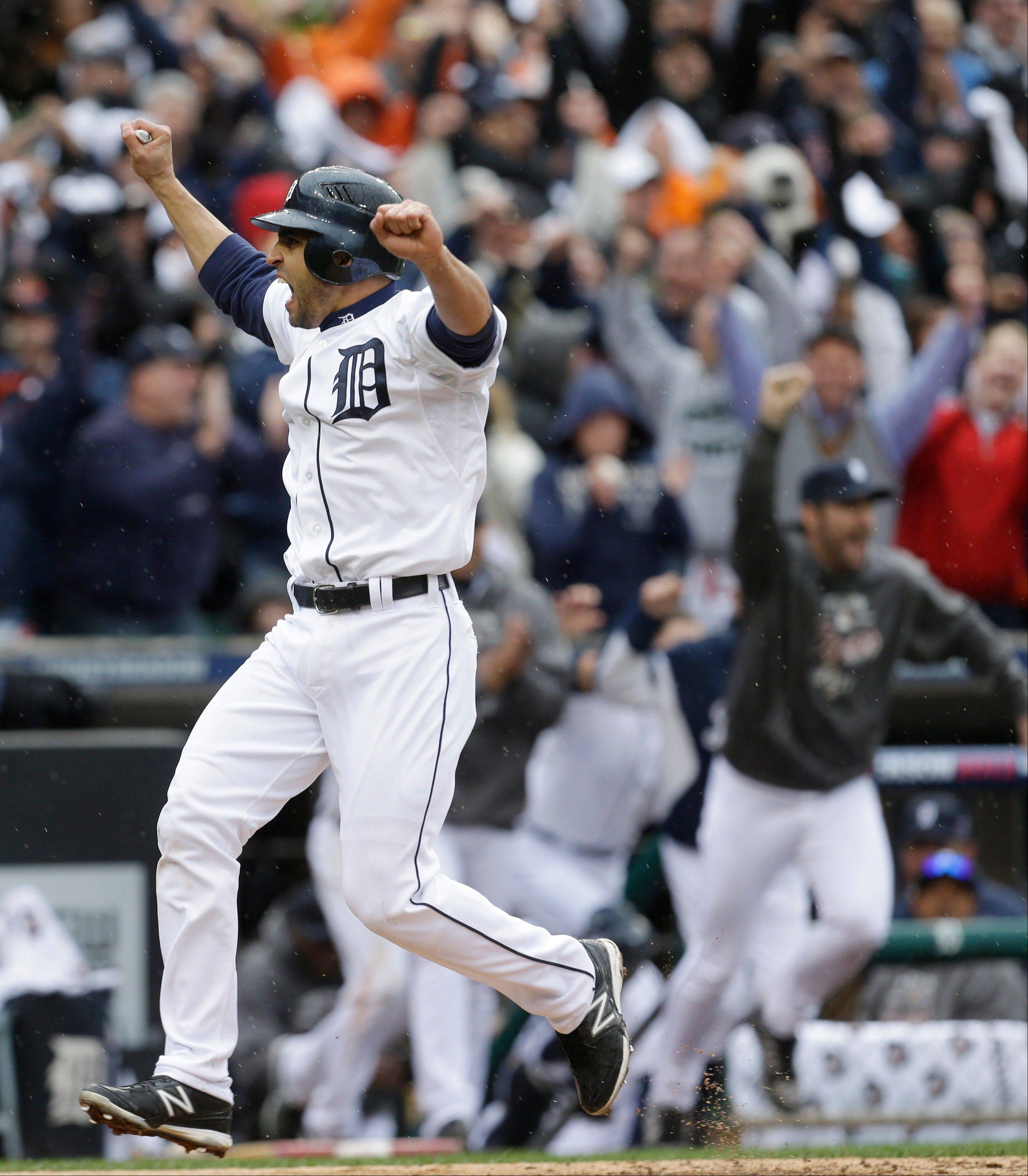 Detroit�s Omar Infante scores the winning run in the ninth inning Sunday on a sacrifice fly by teammate Don Kelly in Game 2 of their American League Division Series against Oakland in Detroit.