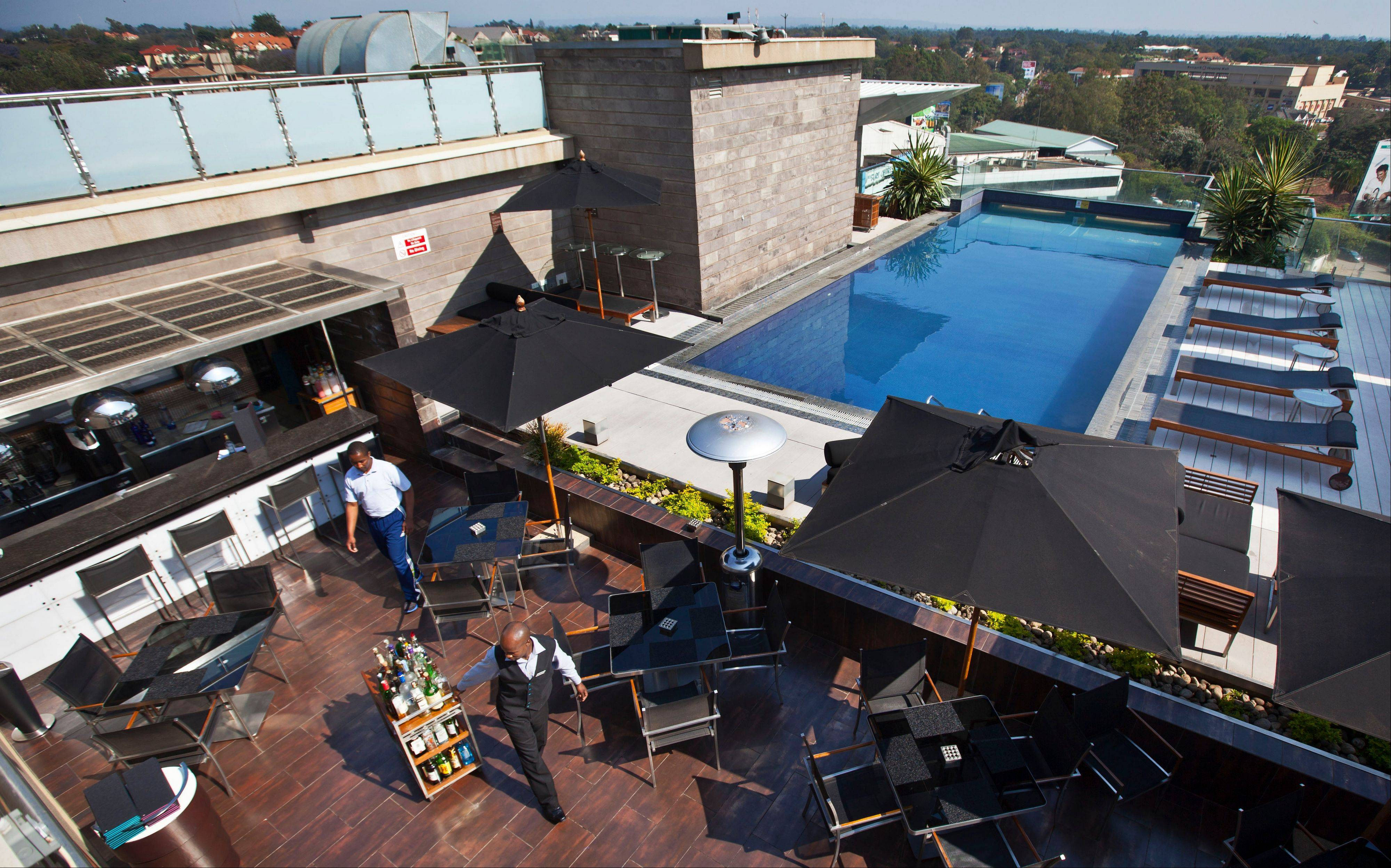 A member of staff wheels drinks at the rooftop pool of the Sankara Nairobi hotel in Nairobi, Kenya. International hotel developers are planning nearly 40,000 new rooms across Africa in the coming years, the continent's business travel is increasing, and Africa's middle class will soon begin leisure travel en masse.