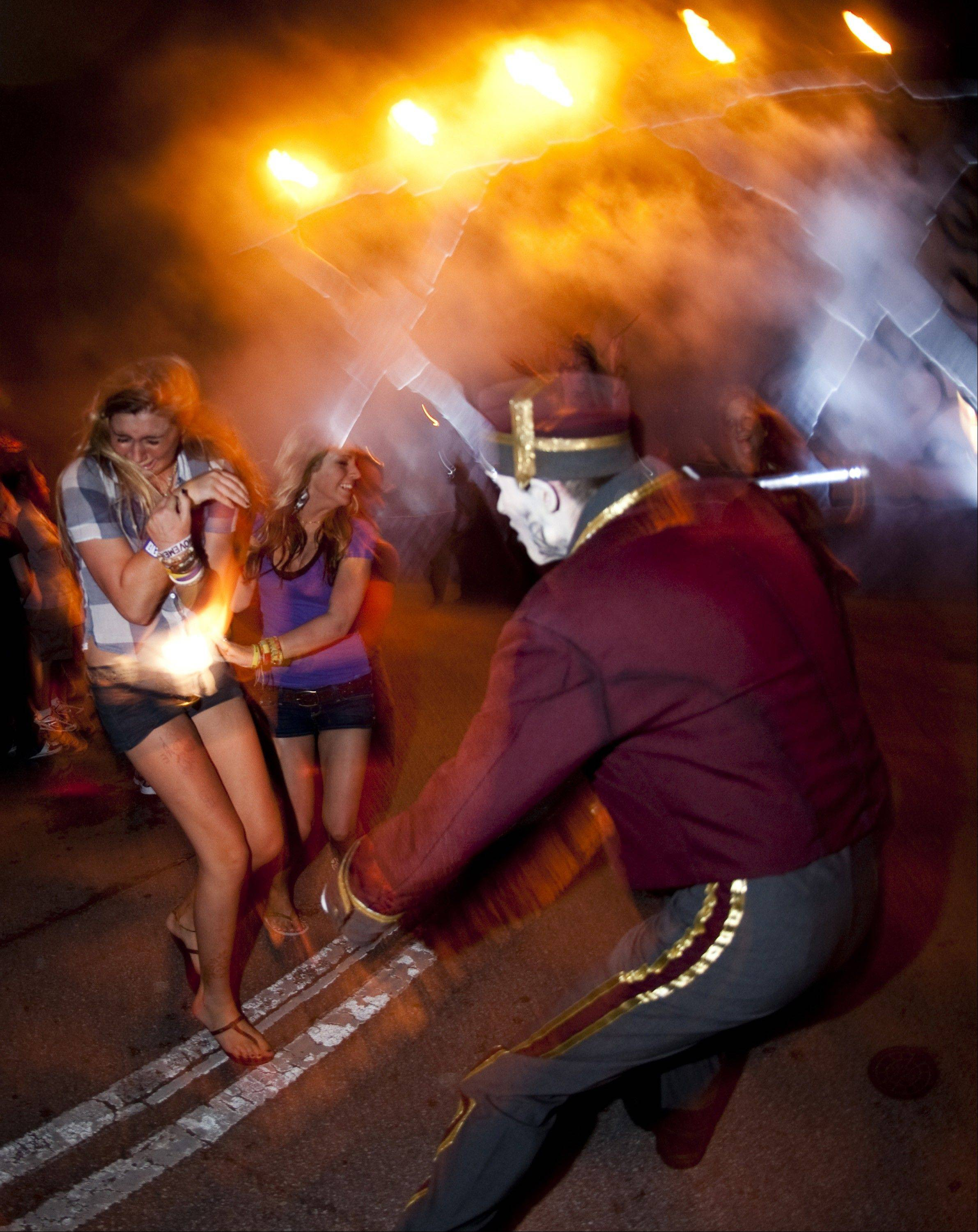 "Visitors react to the ""Usher"" character at Halloween Horror Nights at Universal Orlando Resort in Orlando, Fla."