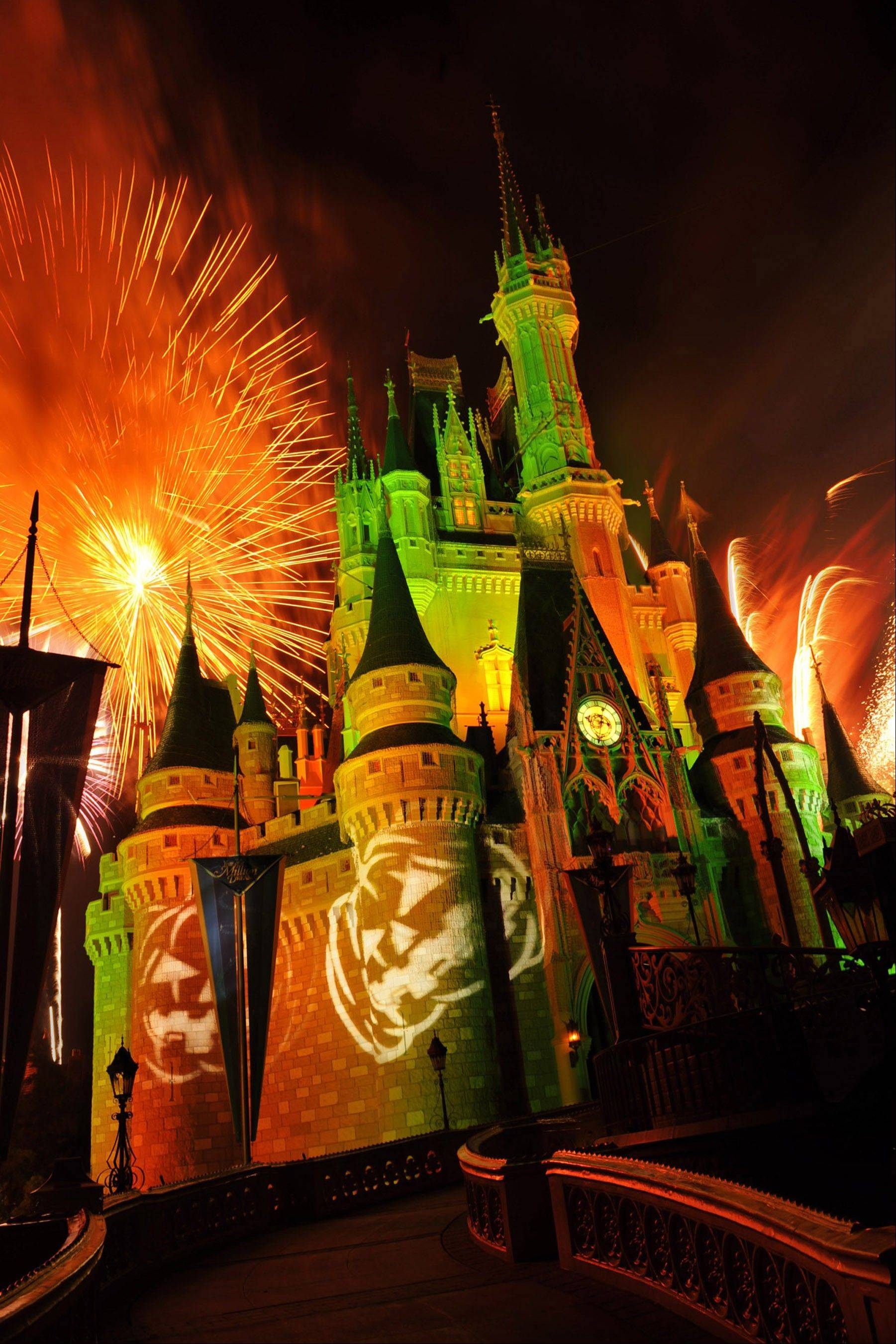 "Orange fireworks explode over Cinderella's Castle while illuminated pumpkins are projected with light during the ""Happy HalloWishes"" fireworks show at Magic Kingdom in Lake Buena Vista, Fla."