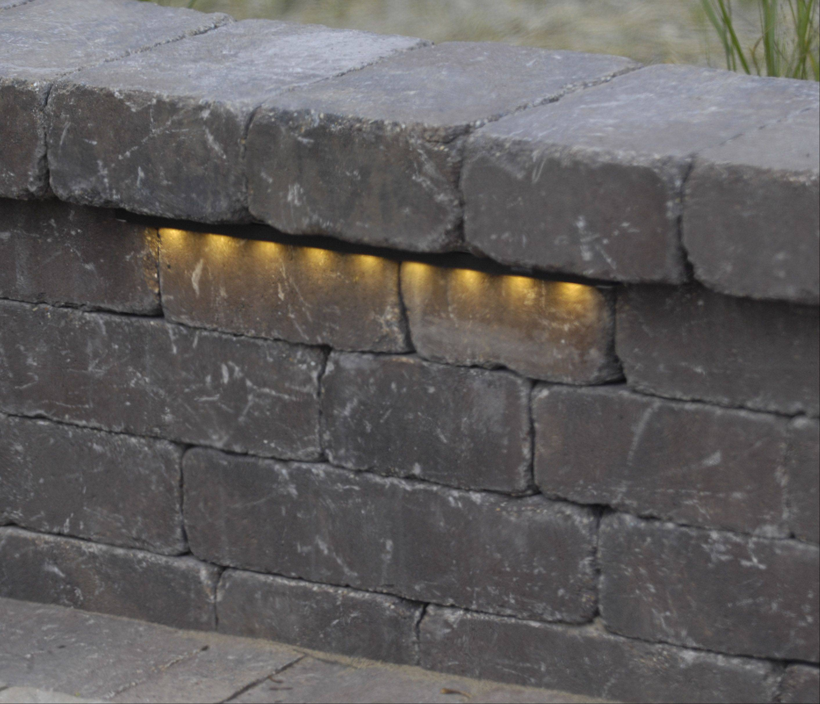 Lighting in the Zeecks' back yard includes subtle glows from the Belgard seatwall around the firepit.