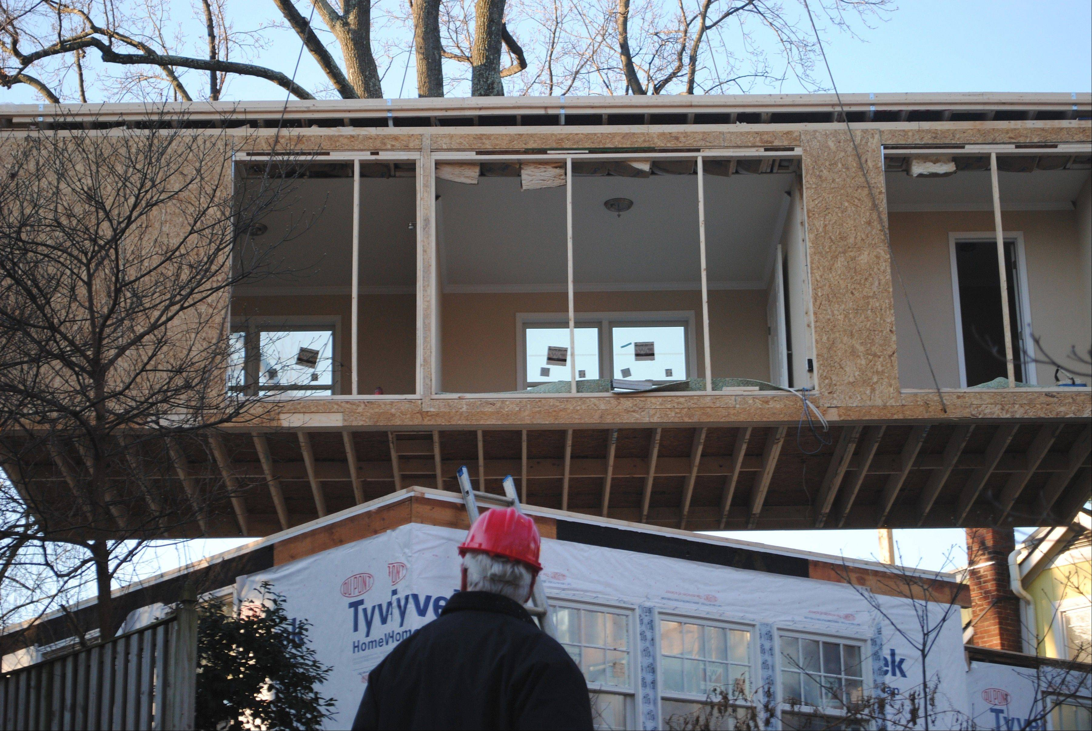 A prefabricated module is hoisted atop the Washington home of Catherine and Nick Swezey. Pre-made modules are gaining favor as cheaper, faster alternatives to conventional additions.