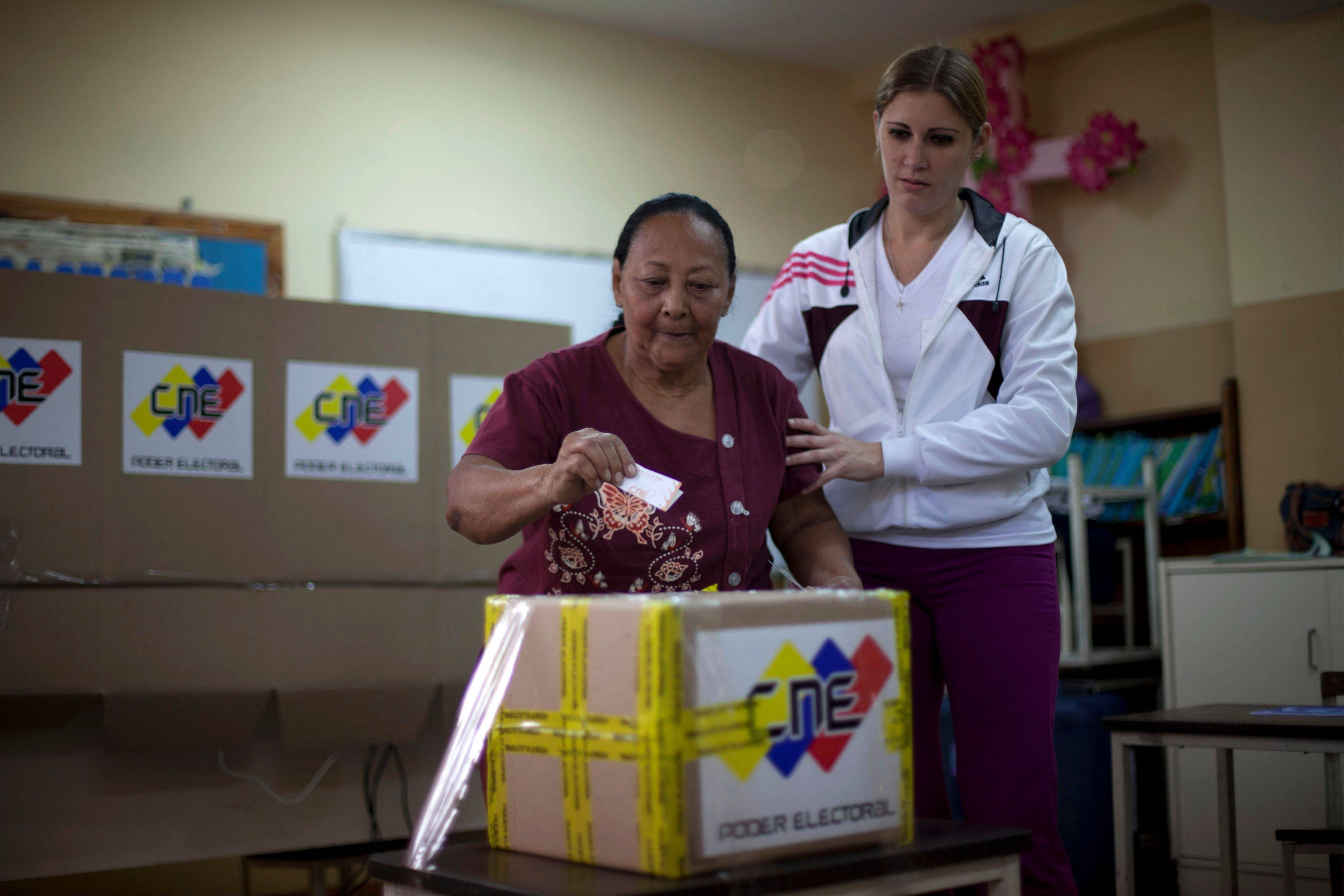A woman is assisted as she puts her ballot in a box during the presidential election at a polling station in Caracas, Venezuela, Sunday, Oct. 7, 2012. President Hugo Chavez is running for re-election against opposition candidate Henrique Capriles.