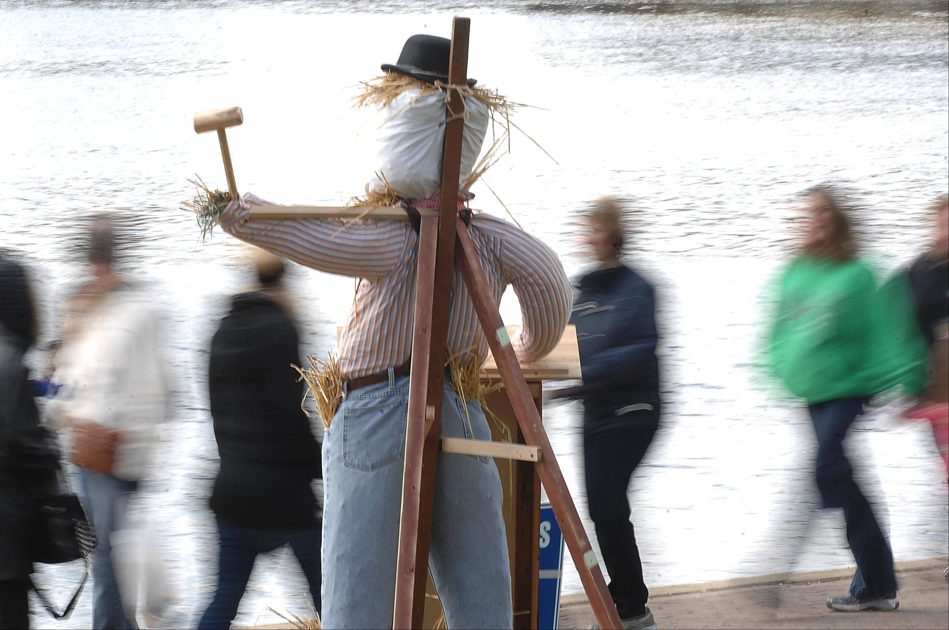 People walk past one of the competition scarecrows on display on the Riverwalk Sunday during the Scarecrow Festival in St. Charles.
