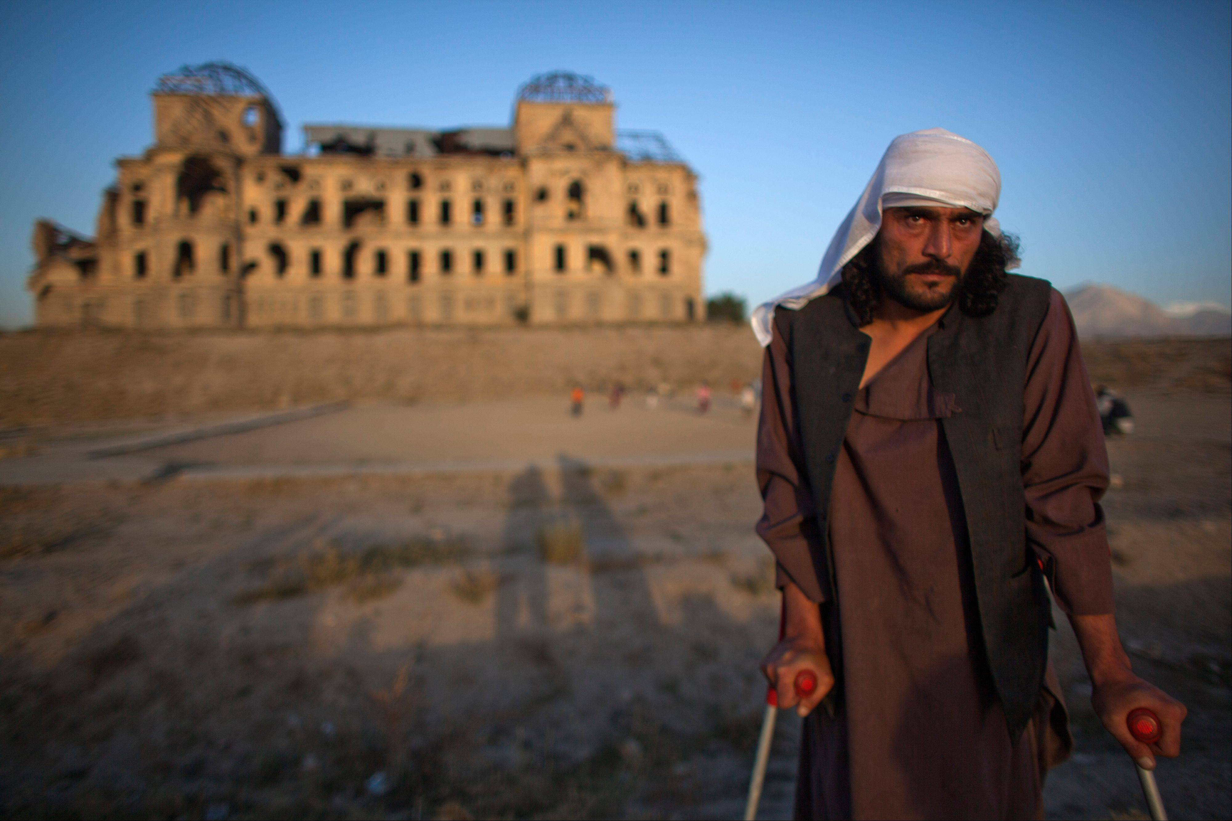 In this Thursday, Oct. 4, 2012 photo, Wahidullah, 32, whose spine was pierced by a bullet during the civil war that left him crippled, poses for a photograph in front of Darul Aman Palace which was damaged during the civil war in Kabul, Afghanistan. Wahidullah was a teenager when he fought in west Kabul during the civil war.