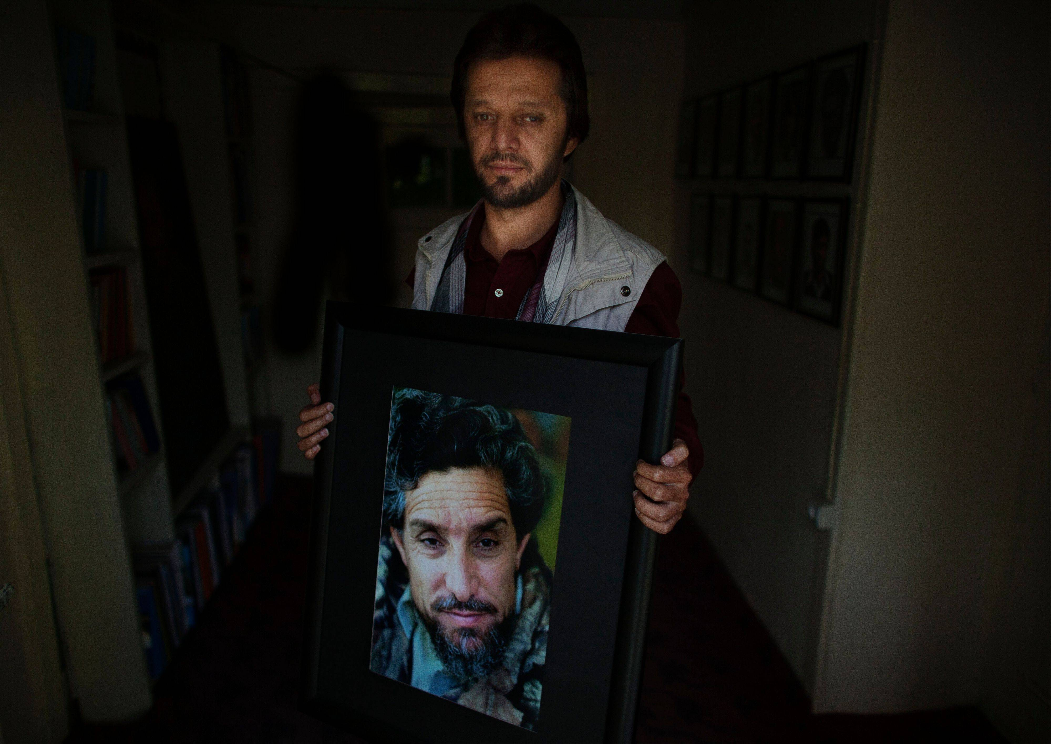 In this Wednesday, Oct. 3, 2012 photo, Fahim Dashti, executive of the National Journalists' Union, poses with a photograph of his wartime leader Ahmad Shah Massoud in Kabul Afghanistan. Dashti was with Massoud, the charismatic Tajik leader who commanded the Northern Alliance, when he was fatally wounded by two terrorists posing as journalists two days before the Sept. 11 attacks.