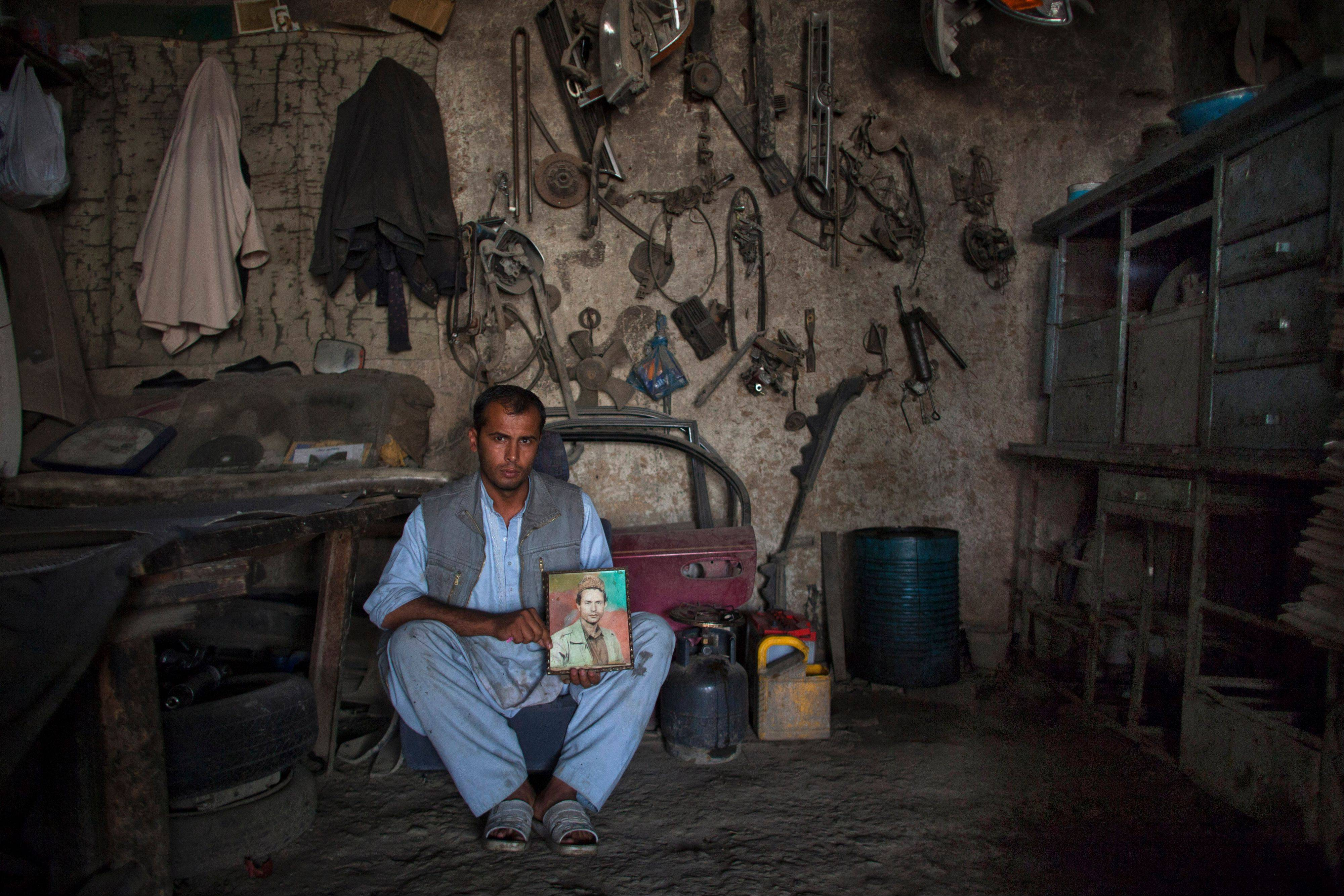 In this Saturday, Oct. 6, 2012 photo, Shah Ker, 29, a car mechanic, poses in the shop he inherited from his father Ramdil Shah who was killed during the Afghan civil war in 1993 in Kabul, Afghanistan.