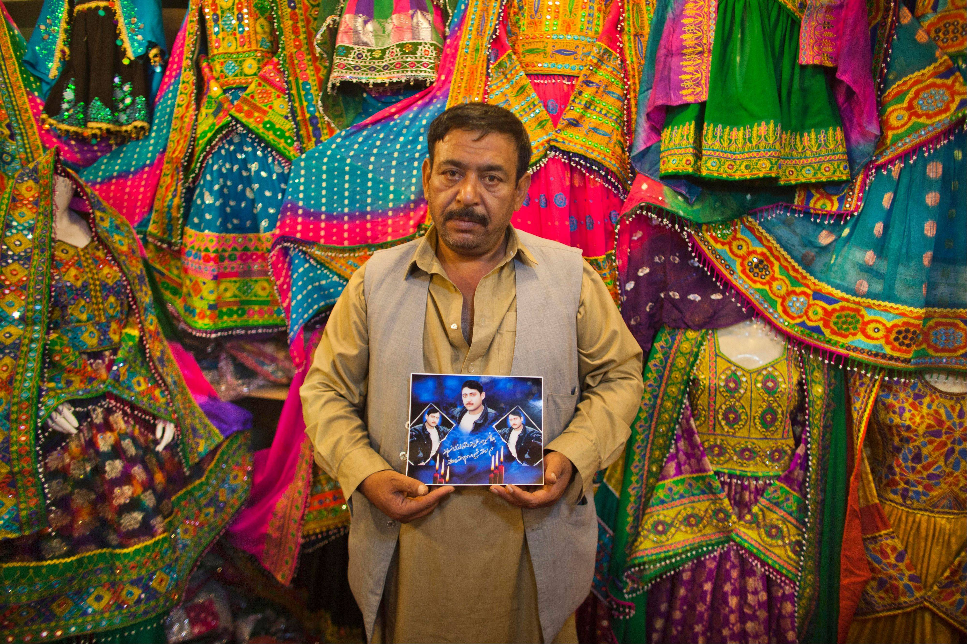 Noorullah Hamidi who owns a women's dress shop, poses with a photograph of his brother Hafizullha, who was killed near the shop while trying to flee street fighting during the civil war in Kabul, Afghanistan, Sunday, Oct. 7, 2012.