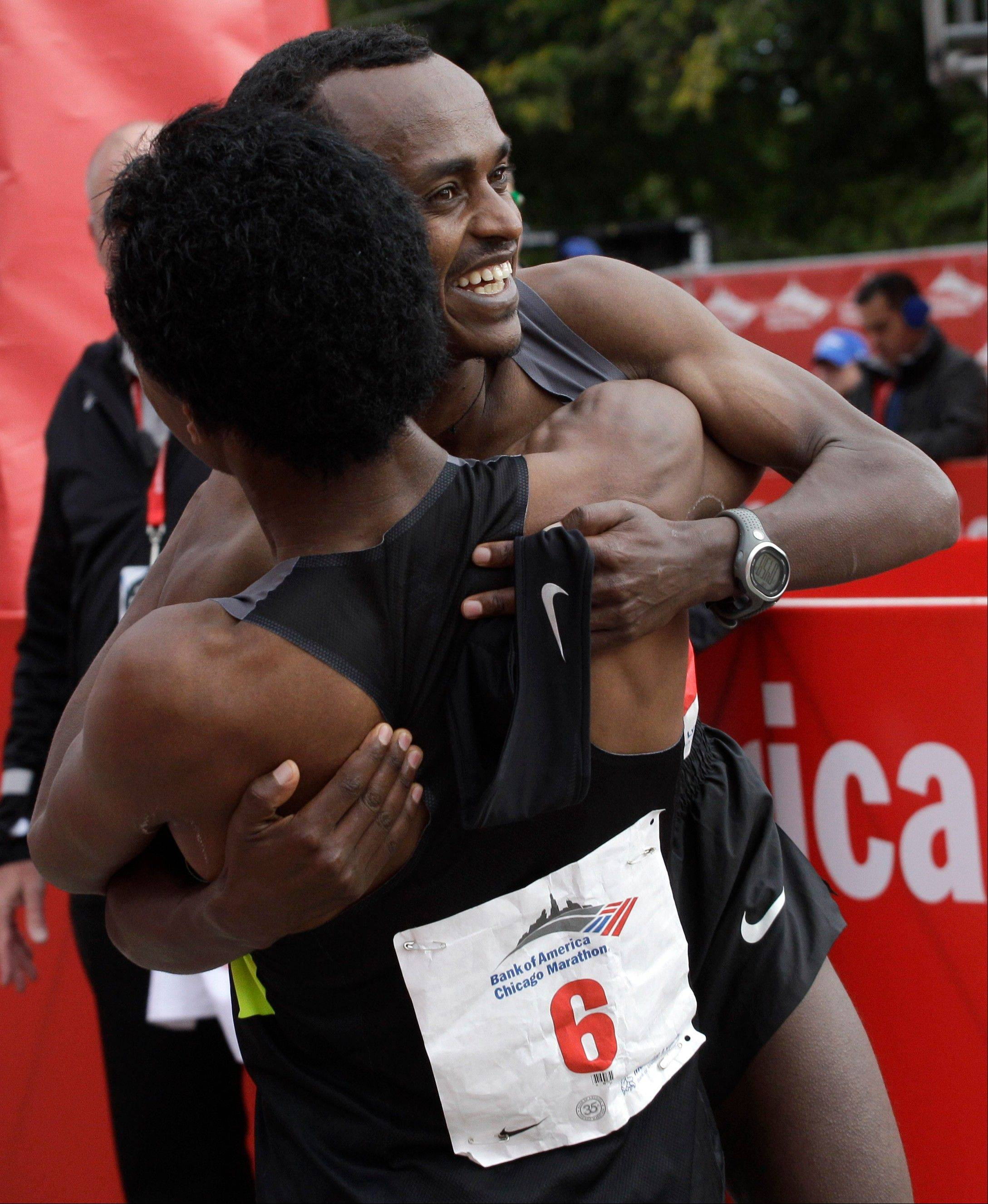 Tsegaye Kebede back, celebrates with fellow Ethiopian Feyisa Lilesa (6), after Kebede won first place and Lilesa finished second in the 2012 Chicago Marathon Sunday, Oct. 7, 2012.