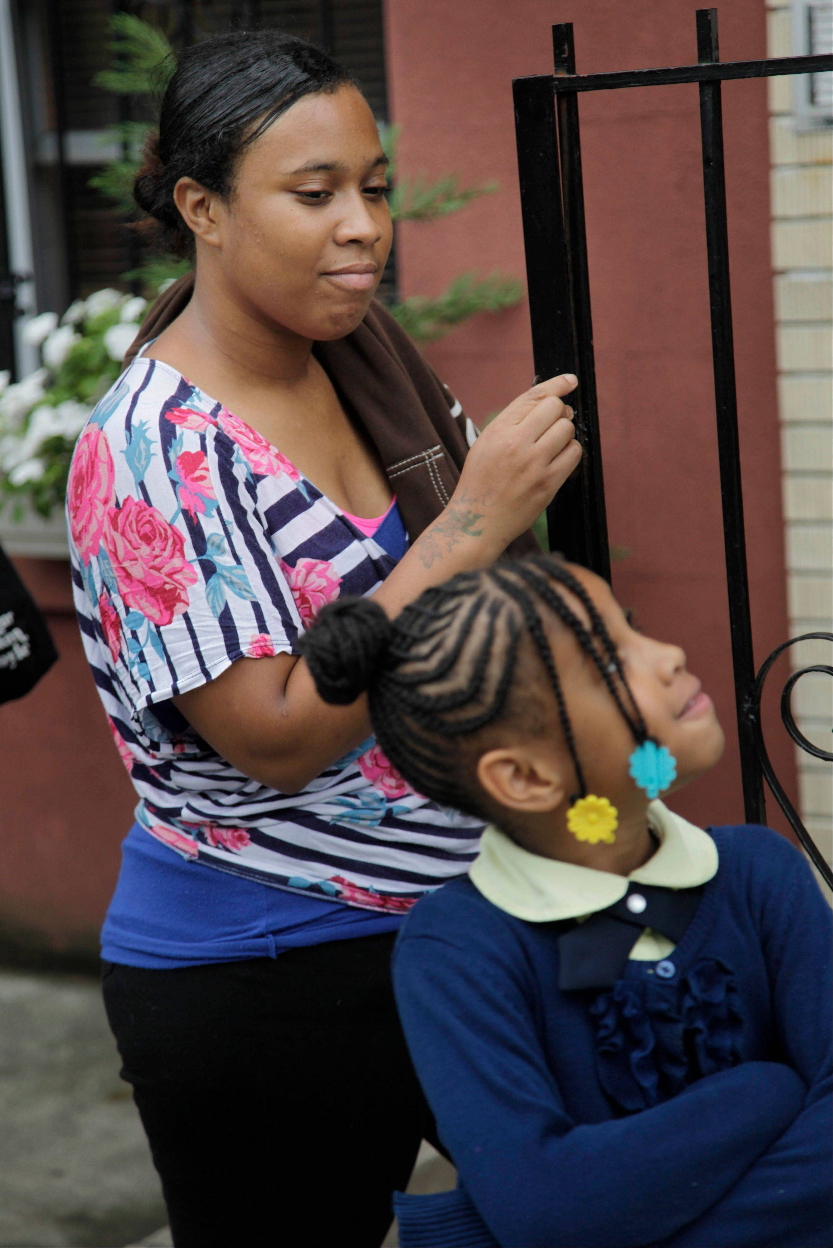 Olgita Blackwood watches her daughter, Malaysia, 7, while waiting for her son to return from school at their apartment in the Drew House in New York.