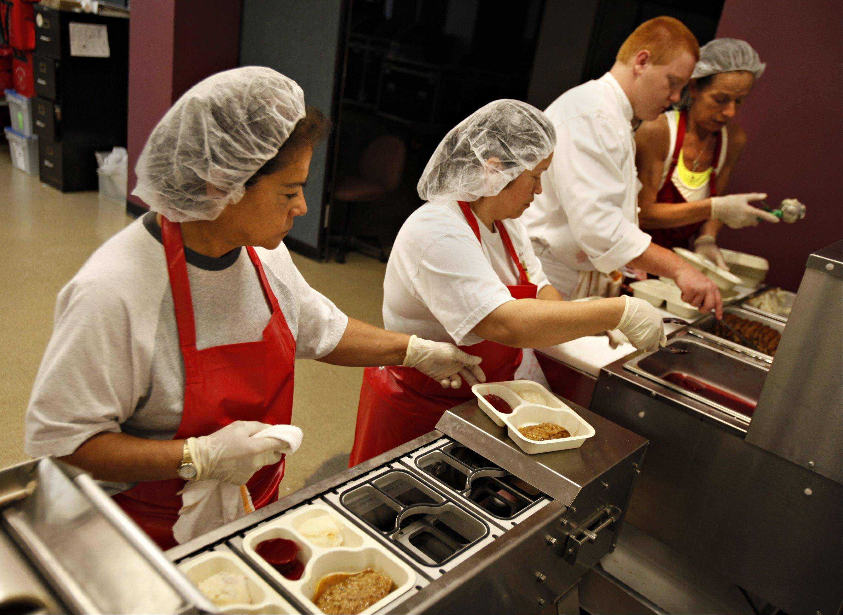Golden Diners employees Yolanda Cruz, left, Raquel Herrera, chef Alex Modaff and Soni Stevens prepare meals on an assembly line. The hot meals are placed on a conveyor, which seals them in plastic before they are boxed up for delivery. Modaff is from Batavia; the others are from Elgin.