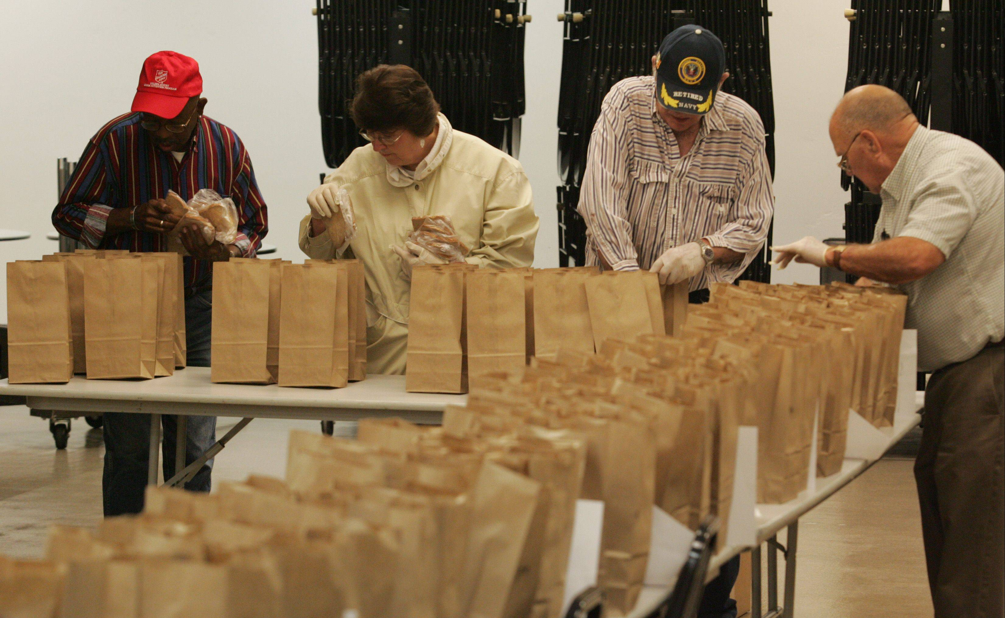 Volunteers and employees at the Salvation Army Golden Diners program fill lunch sacks with sandwiches at the Hemmens Cultural Center in downtown Elgin. From left are Leslie Thomas of Elgin, Sue Feikema of West Dundee, and Frank Plushkis and Gordon Roe, both of Elgin.