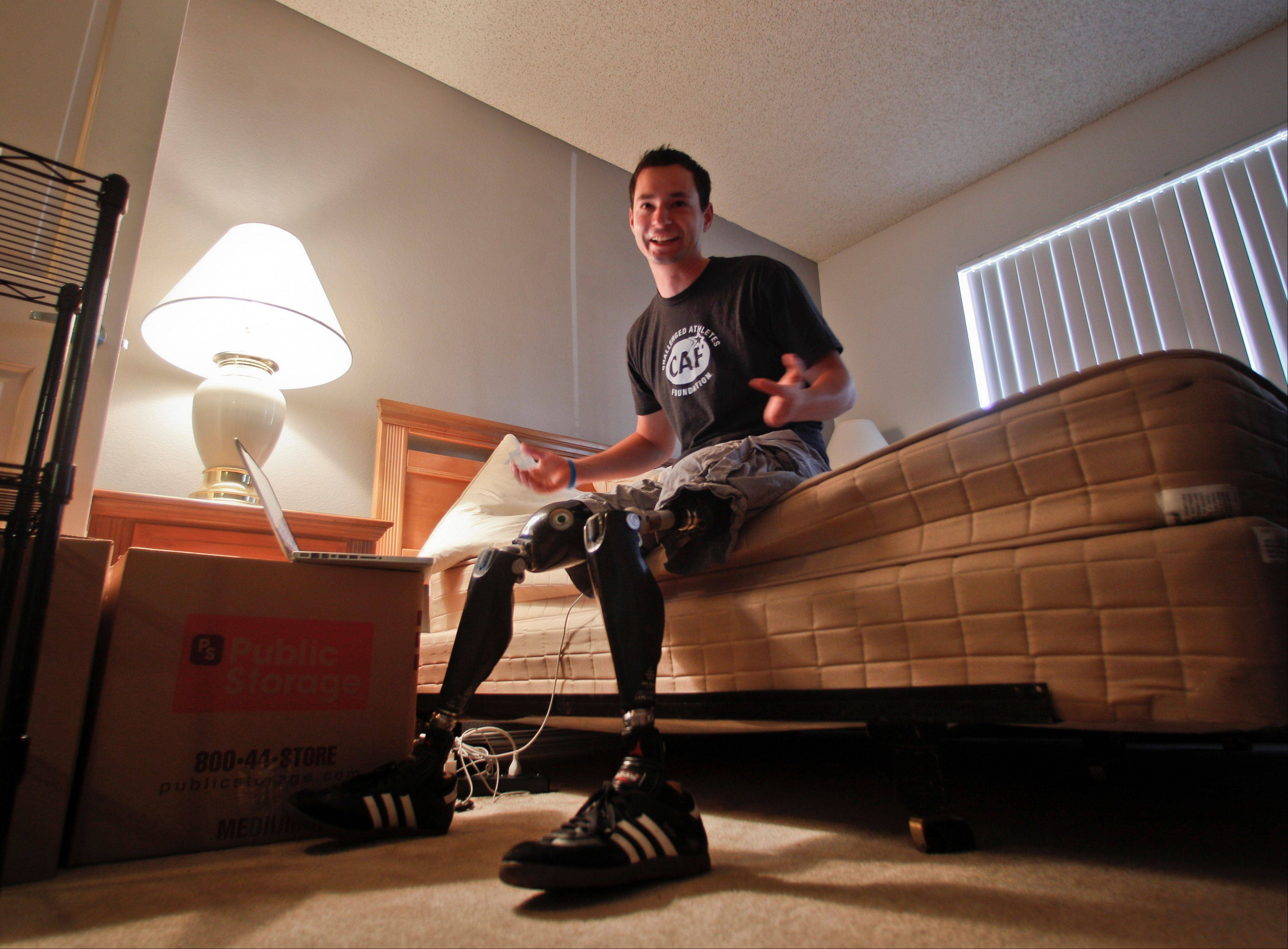"Former U.S. Marine Cpl. Daniel Riley, 21, sits on his bed Thursday with his belongings packed for storage as he prepares for a lengthy trip that will take him as far as New Zealand. Learning to walk on his prosthetic legs was ""like kicking a soccer ball in a swimming pool."" But he didn't just learn to walk; he has learned to soar. He joined ""Operation Rebound,"" and has graduated from competitor to mentor."