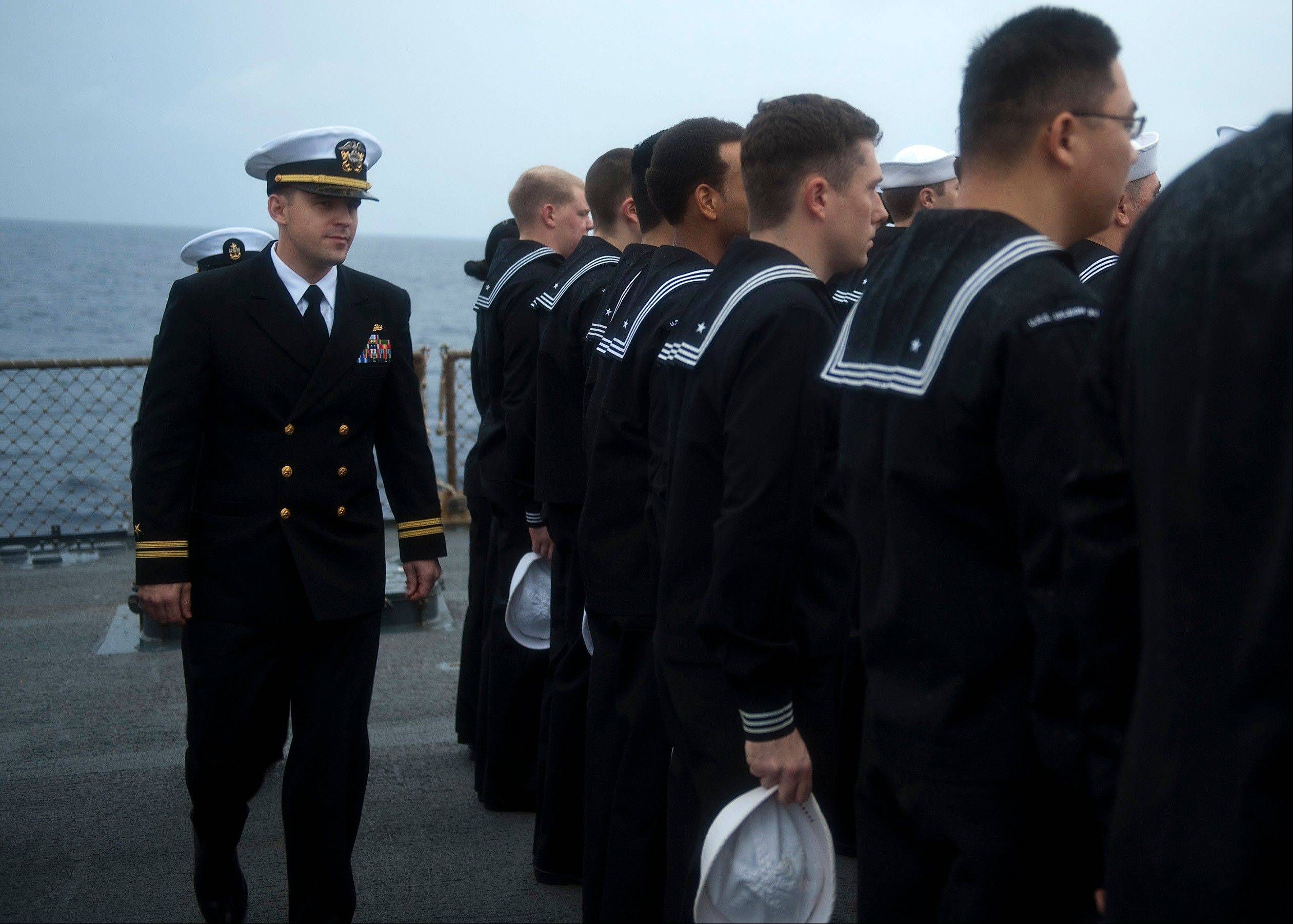 Lt. Joshua Welle, chief engineer for the guided-missile destroyer USS Arleigh Burke, inspects engineering department Sailors' dress blue uniforms after an exercise in the Atlantic Ocean. As president of a class of 980 midshipmen, Welle had heard about Marine Capt. Matthew C. Freeman. But he did not come to know his classmate until after his death. Welle, a lieutenant commander in the Navy, is back in the States for three weeks' leave. He is using part of that time to travel the country and tell audiences about Freeman and other classmates who have sacrificed in the ongoing War on Terror.