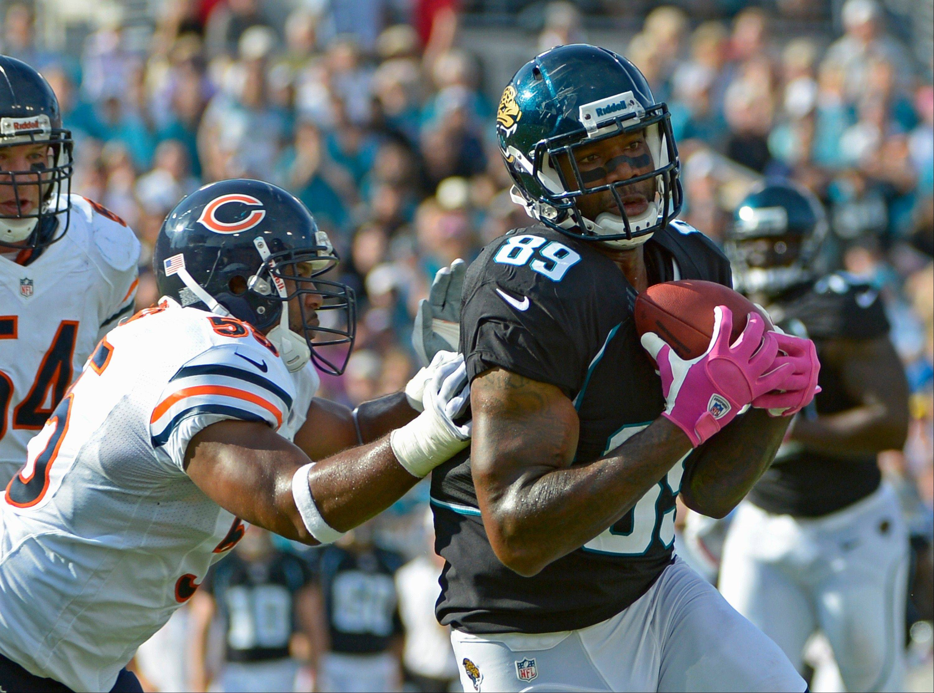 Jacksonville Jaguars tight end Marcedes Lewis catches a pass in front of Chicago Bears outside linebacker Lance Briggs, left, during the first half, Sunday, in Jacksonville, Fla.