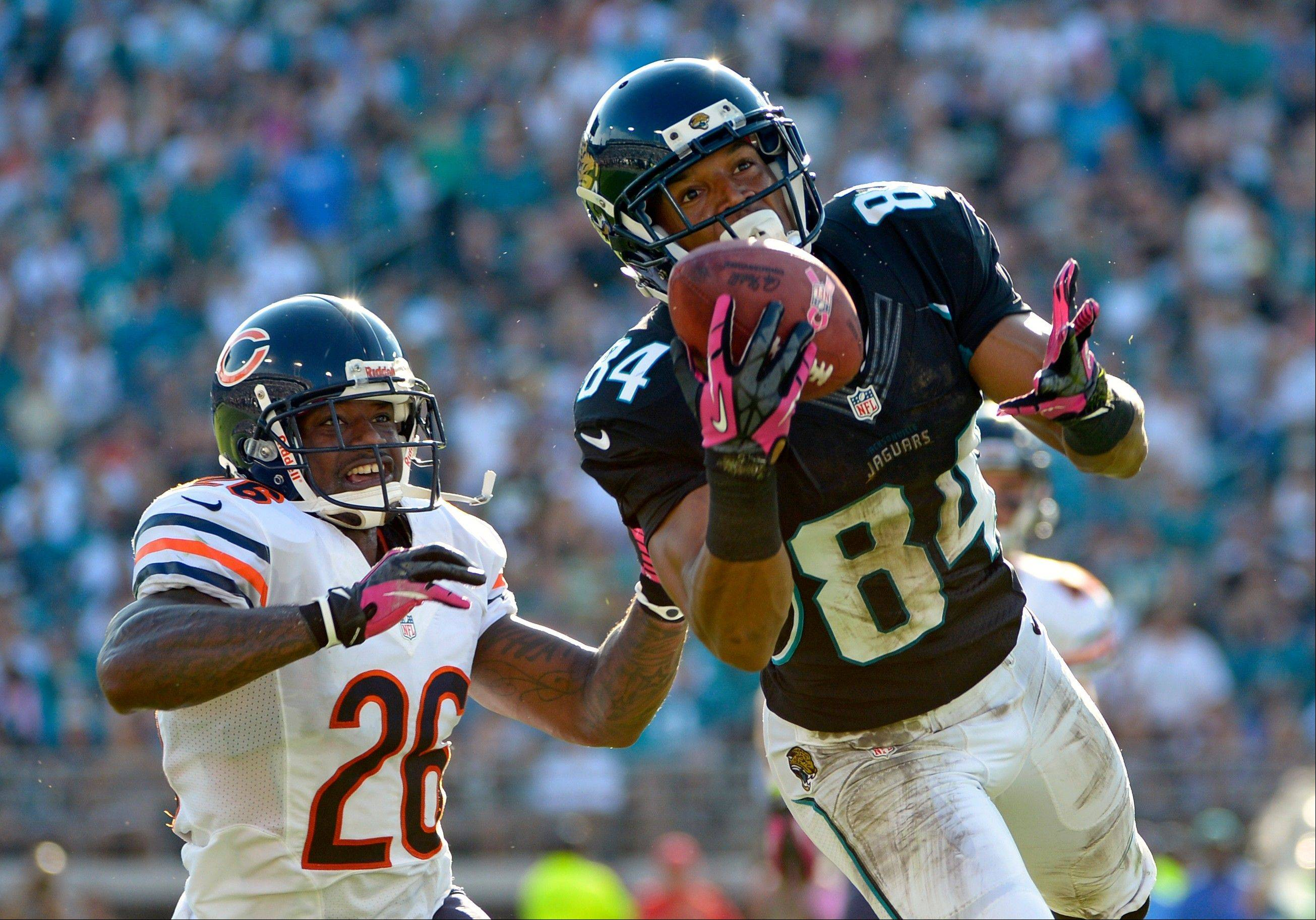 Jacksonville Jaguars wide receiver Cecil Shorts catches a pass for a 34-yard gain in front of Chicago Bears cornerback Tim Jennings during the first half, Sunday, in Jacksonville, Fla.