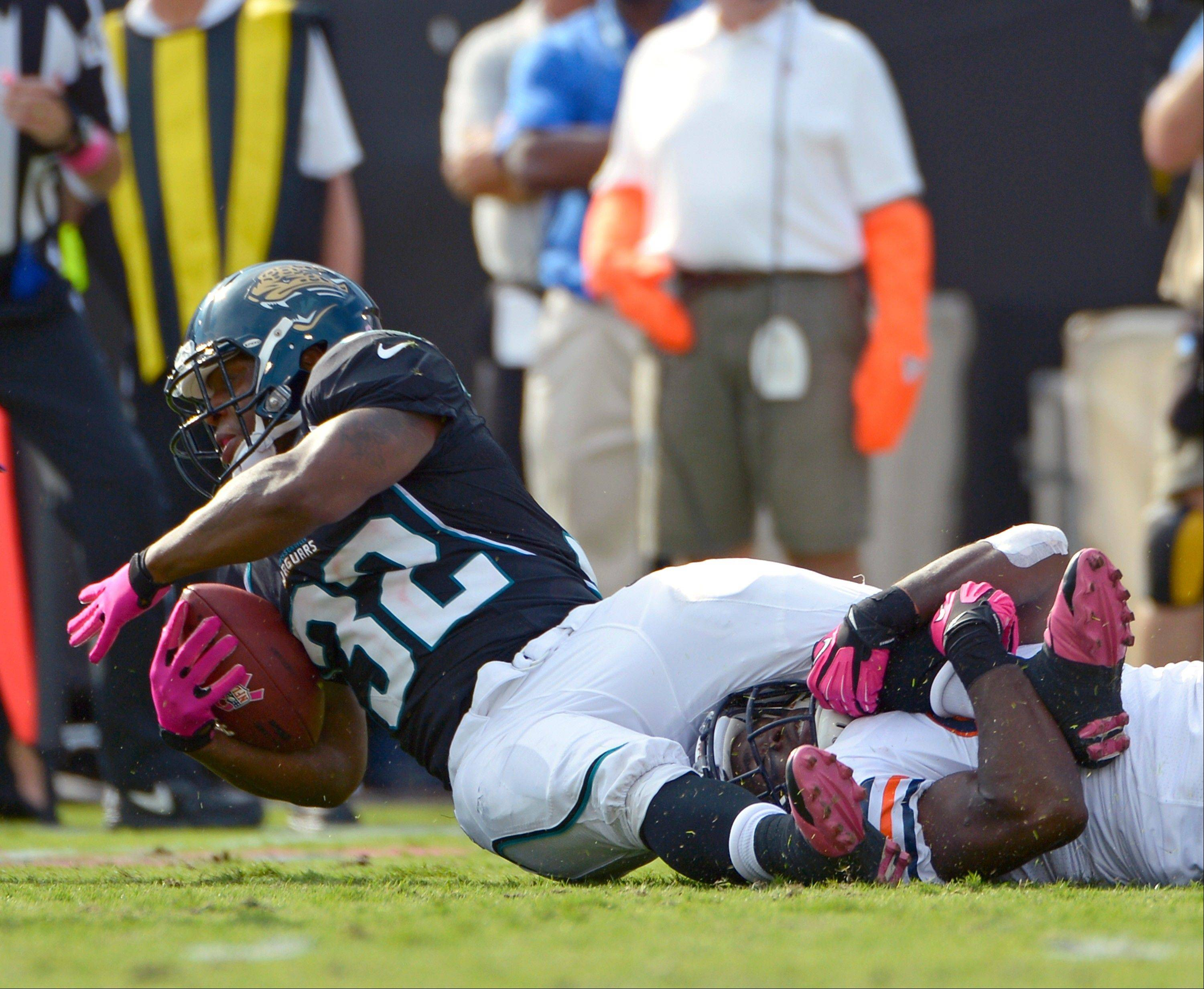 Jacksonville Jaguars' Maurice Jones-Drew is stopped for a short gain by Chicago Bears strong safety Major Wright during the first half, Sunday, in Jacksonville, Fla.