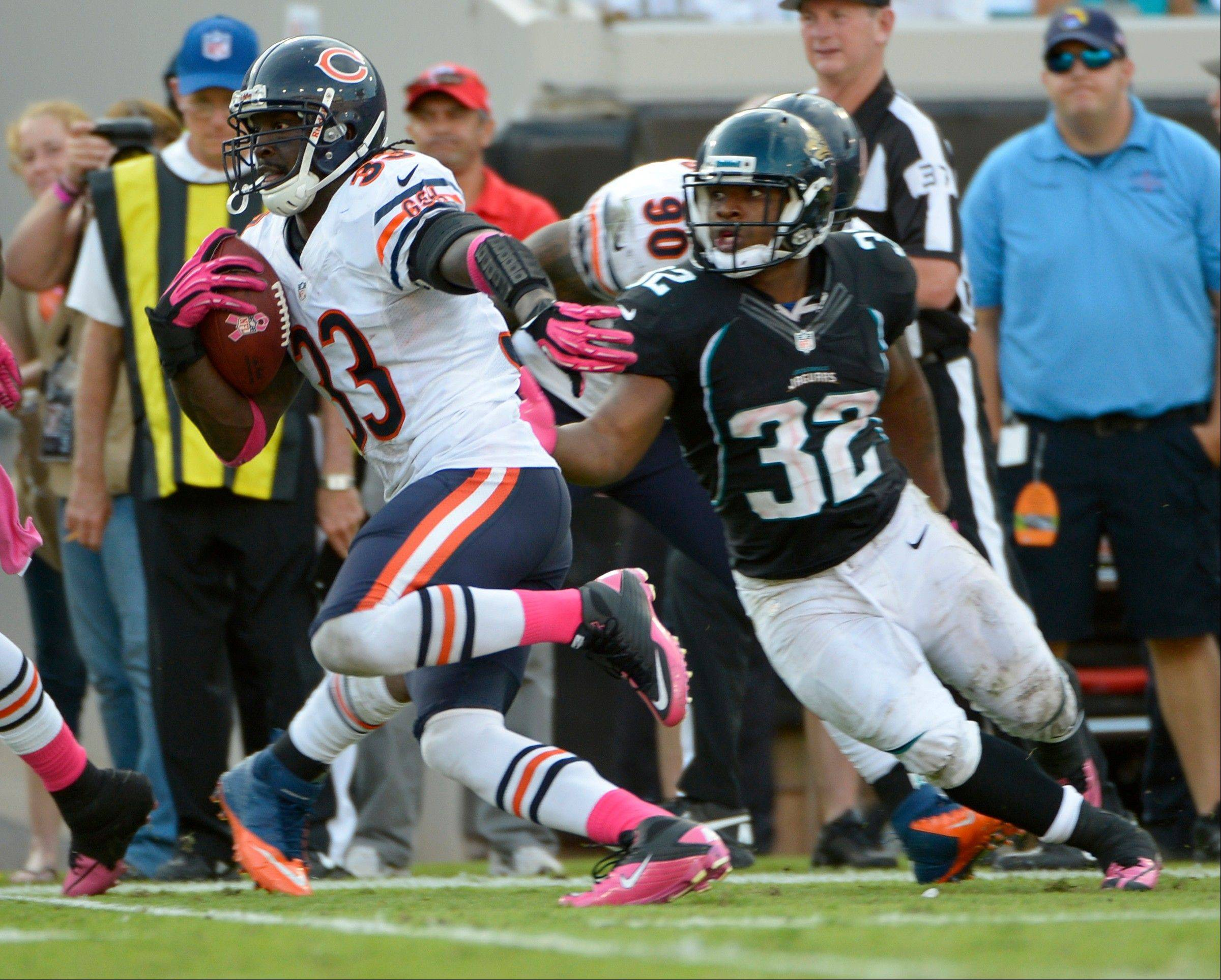 Chicago Bears cornerback Charles Tillman runs past Jacksonville Jaguars running back Maurice Jones-Drew after intercepting a pass for a 36-yard touchdown during the second half of an NFL football game, Sunday, Oct. 7, 2012, in Jacksonville, Fla.