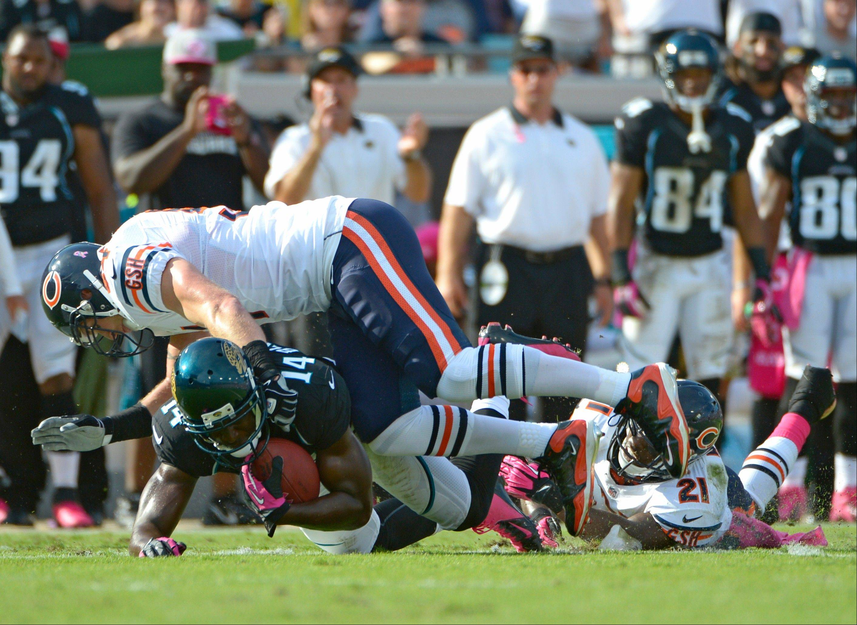 Jacksonville Jaguars wide receiver Justin Blackmon is tackled after a reception by Chicago Bears middle linebacker Brian Urlacher, top, and strong safety Major Wright during the first half, Sunday, in Jacksonville, Fla.