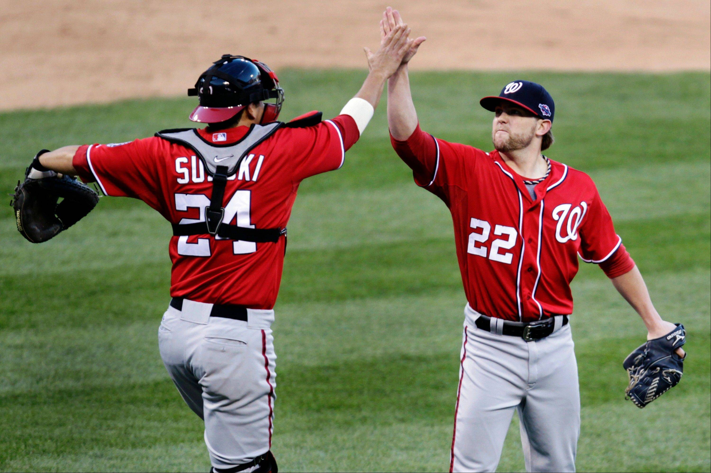 Washington Nationals relief pitcher Drew Storen, right, and catcher Kurt Suzuki celebrate their 3-2 win Sunday over the St. Louis Cardinals in Game 1 of baseball's National League division series.
