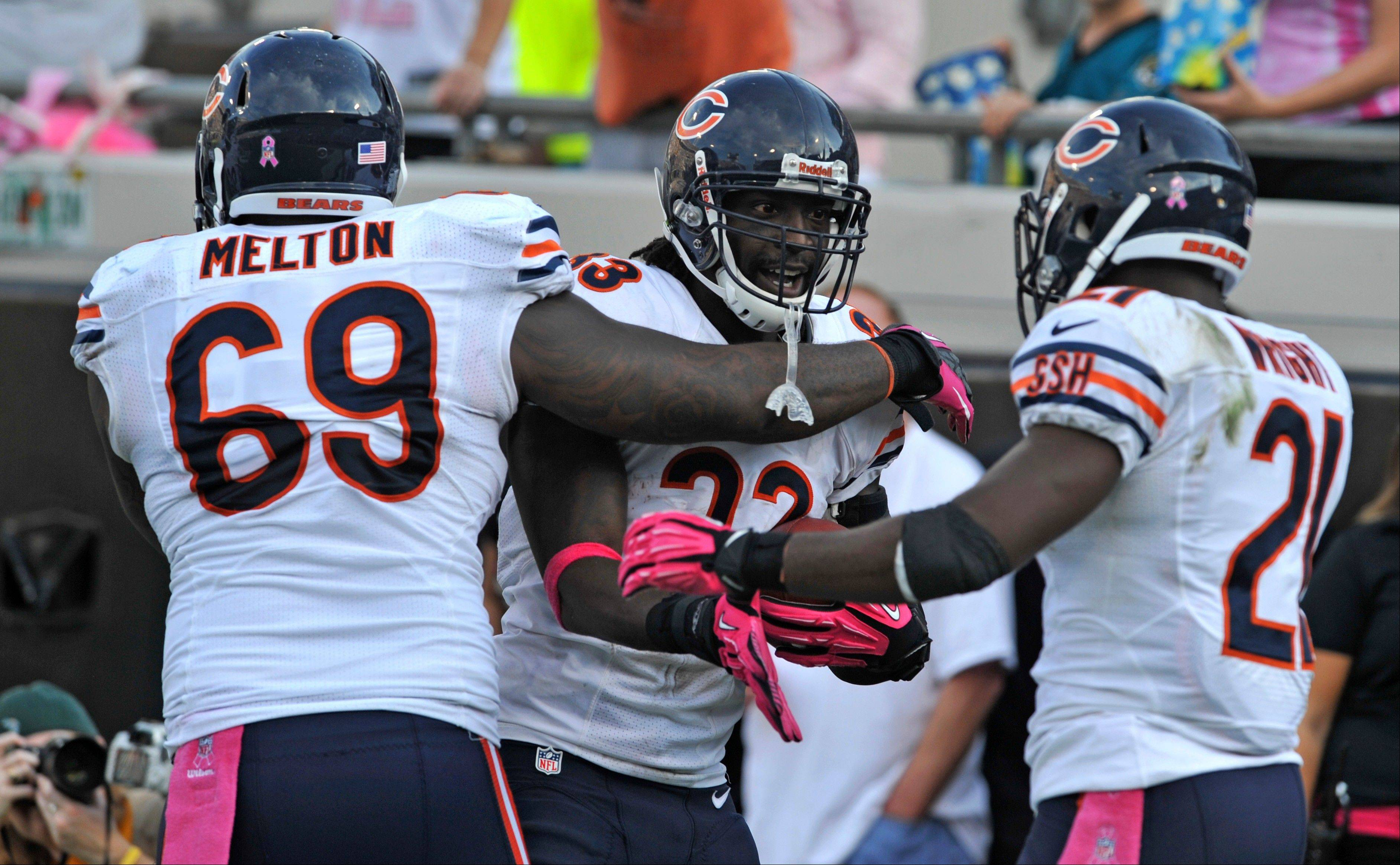 Bears cornerback Charles Tillman, center, celebrates with teammates Henry Melton and Major Wright after intercepting a pass and scoring a 36-yard touchdown in Sunday's second half.