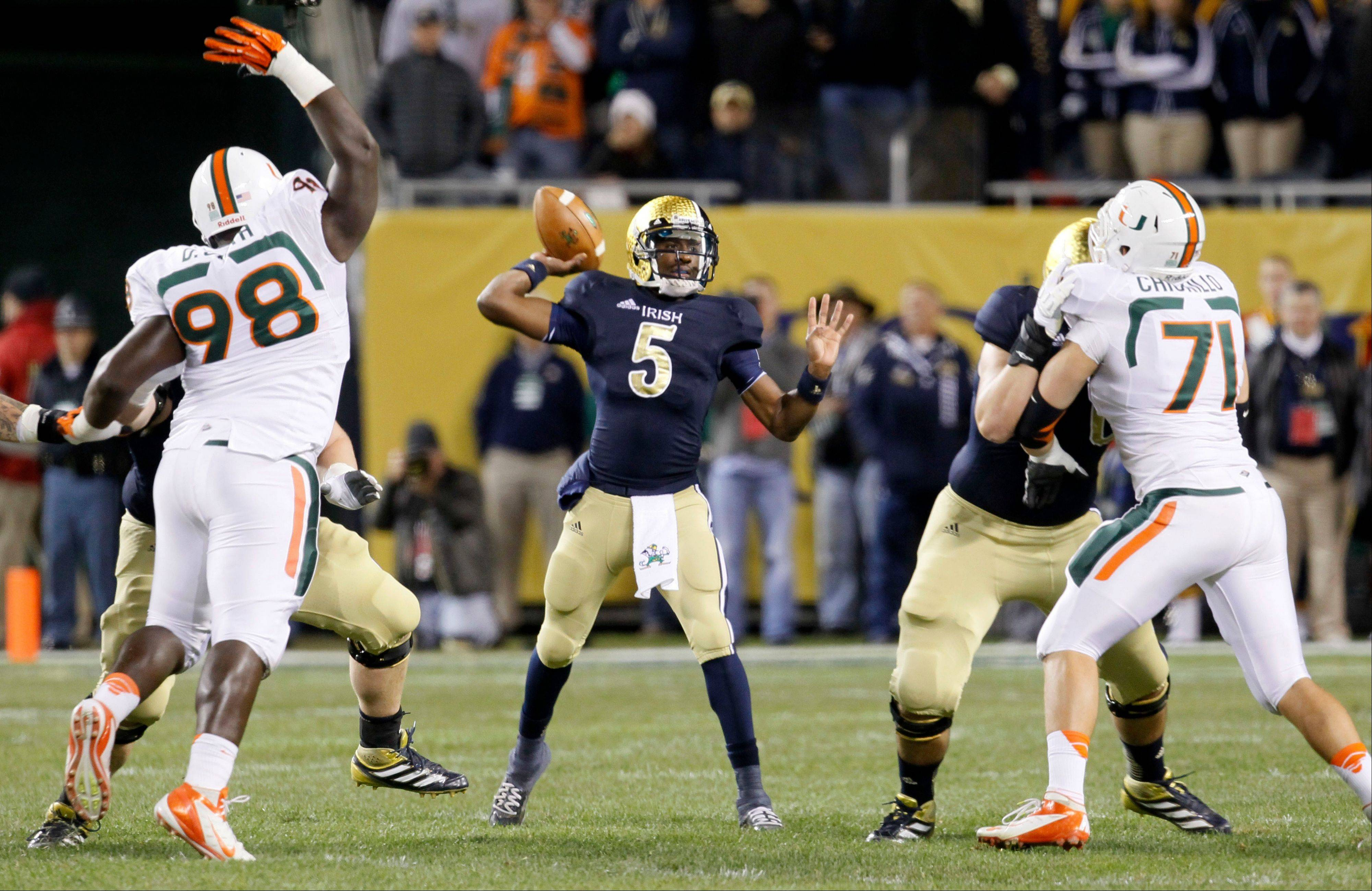 Notre Dame quarterback Everett Golson passes between Miami defensive linemen Darius Smith, left, and Anthony Chickillo during the first half Saturday at Chicago's Soldier Field.